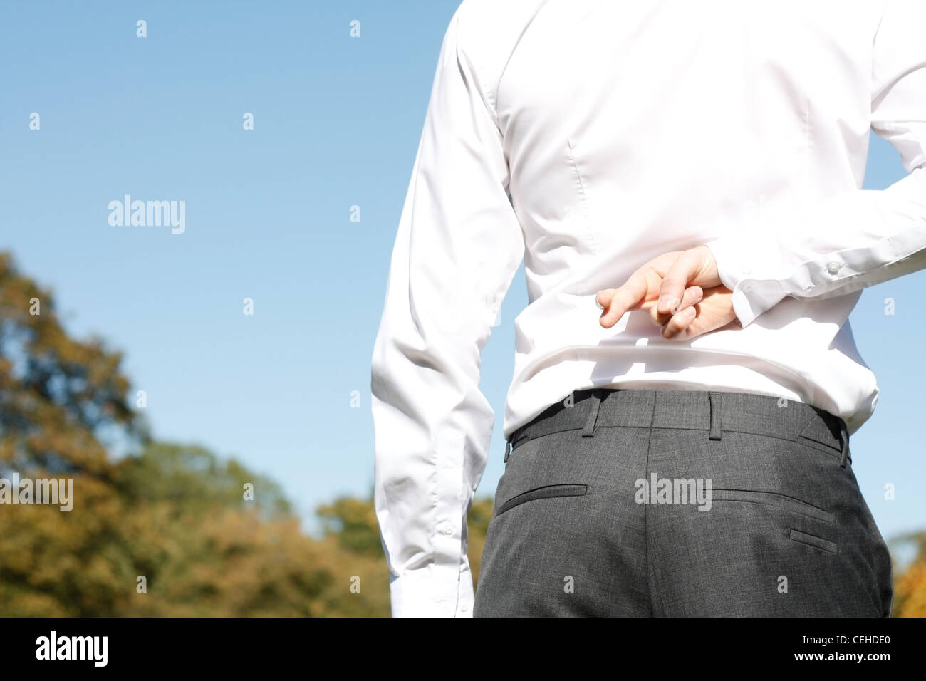 A business man with fingers crossed - Stock Image