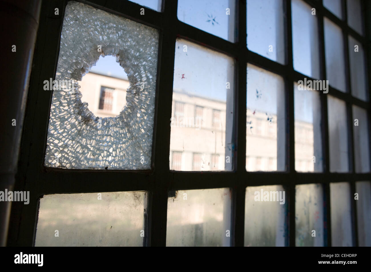 broken window hole glass shattered looking out horizontal - Stock Image