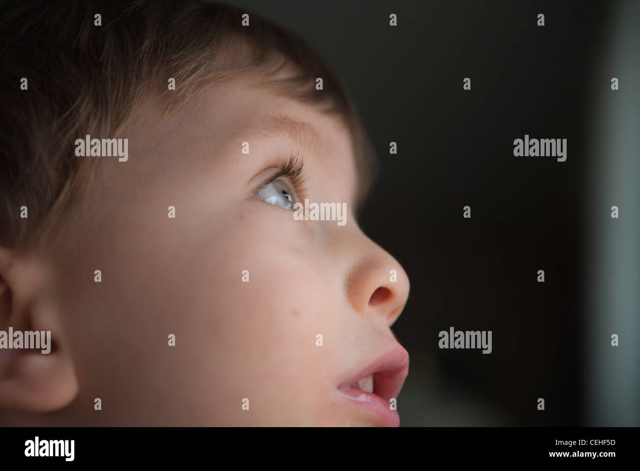 close up of two year old boy looking up through window, profile of face. - Stock Image
