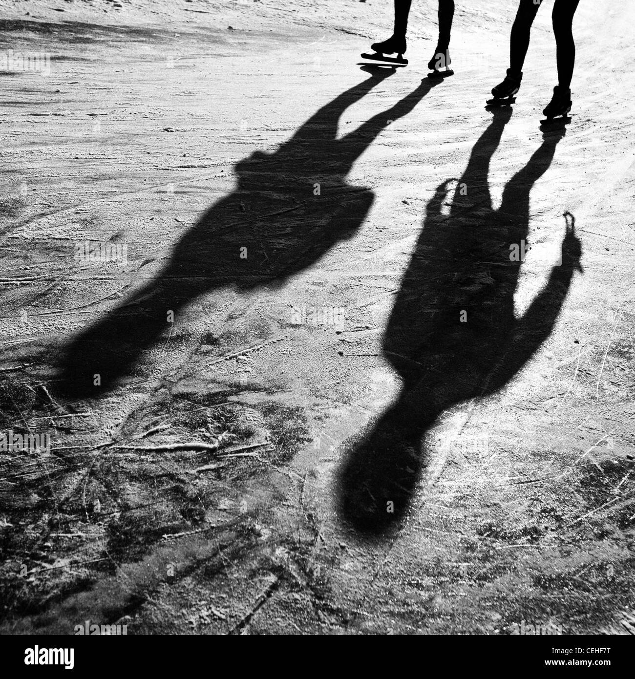 long shadows of two ice skaters looks like aliens - Stock Image