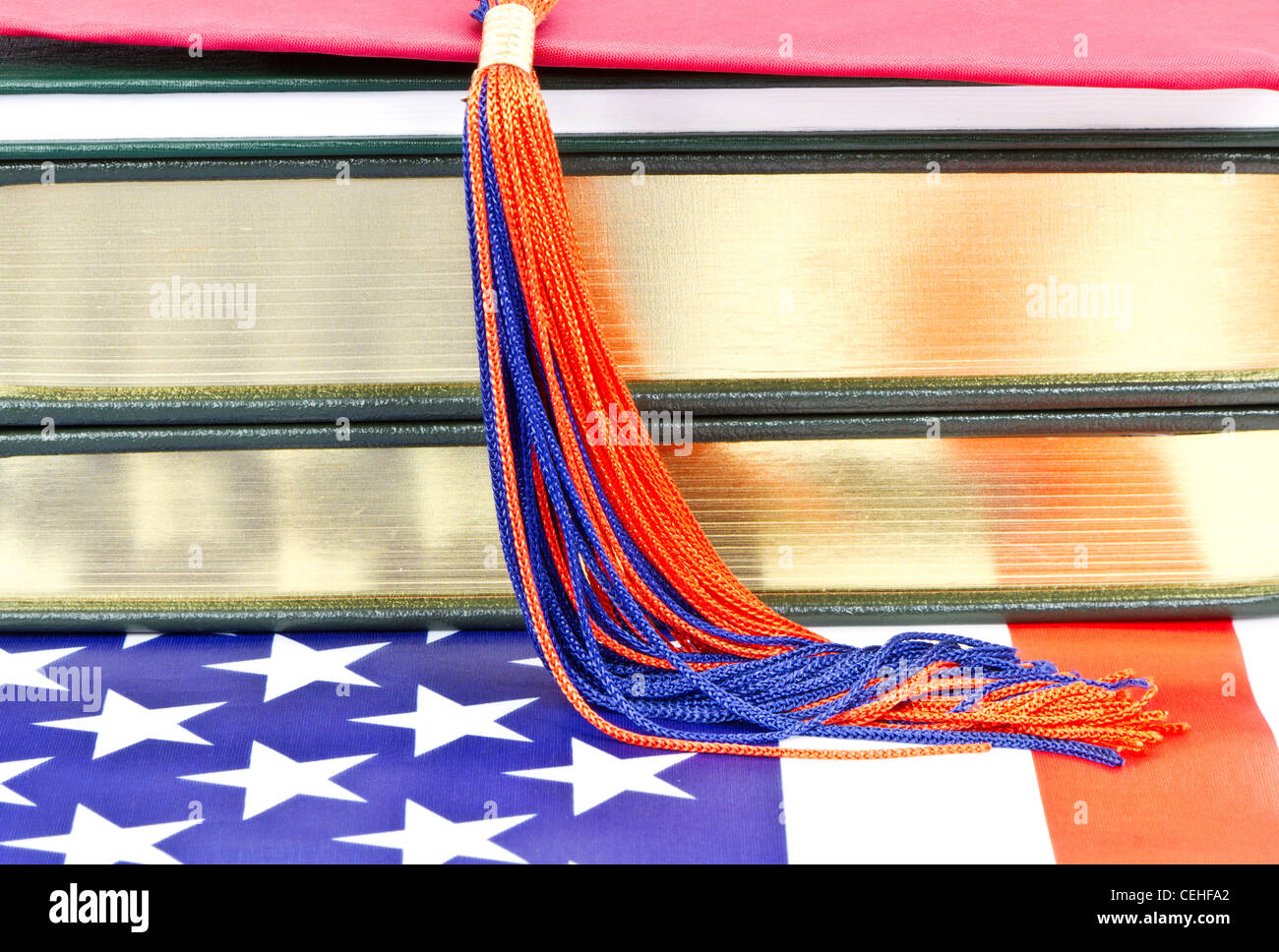 Graduation tassel on top of books placed on American flag symbolize American education, graduation, and its life - Stock Image