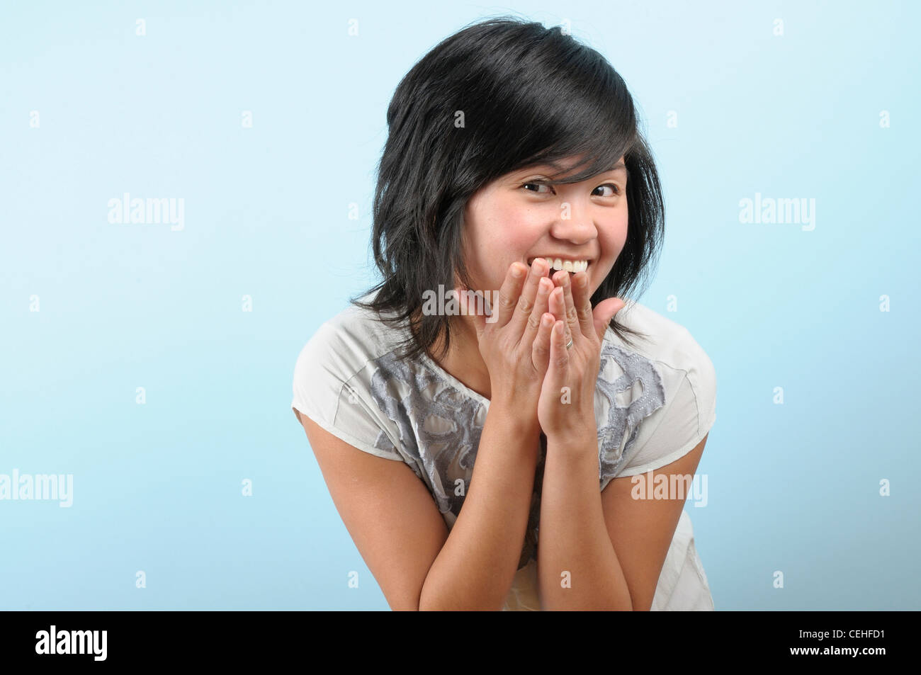 6a4ade56f69 Young Asian woman holds her hands to her face in delight - Stock Image
