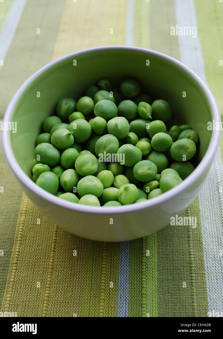 Shelled fresh ripe sweet green peas in a ceramic bowl Stock Photo