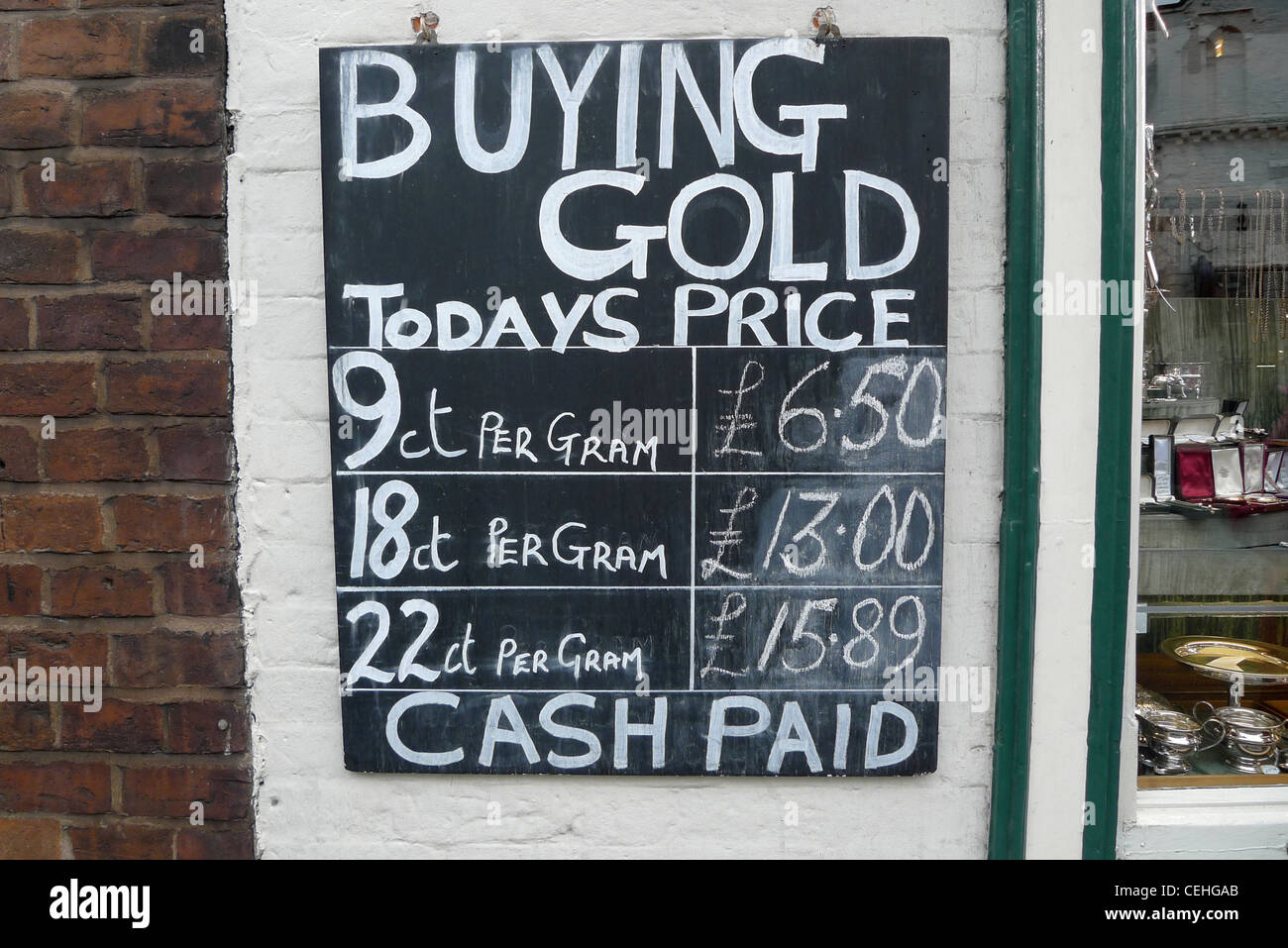 A Buying Gold sign on the exterior of a jewellry shop showing the price of gold in Shrewsbury England UK - Stock Image