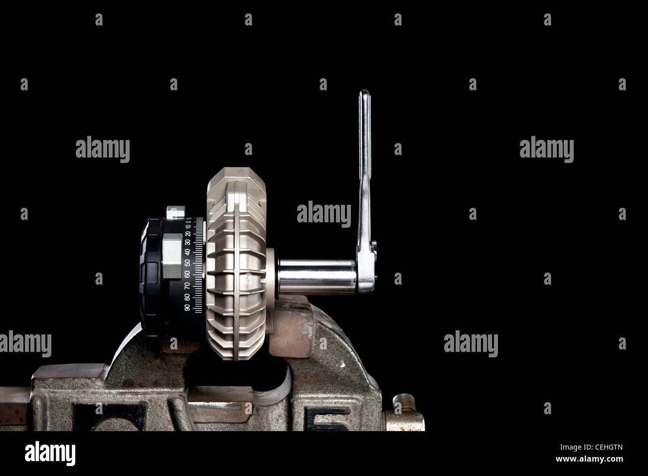 A small mechanical pump in a vice isolated on black for placement of copy. - Stock Image