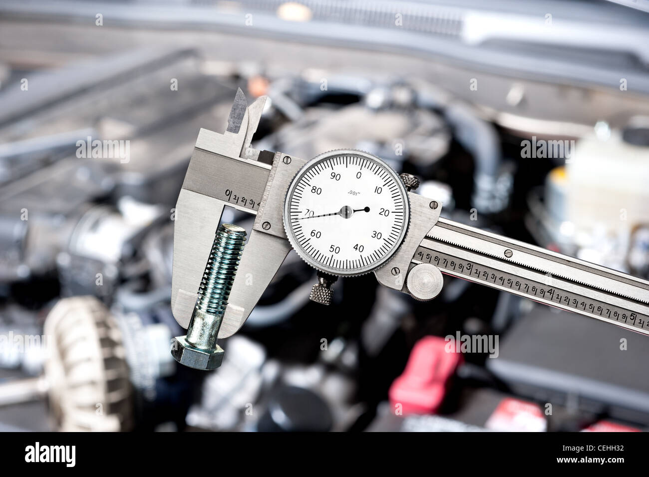 A shiny vernier caliper micrometer in front of a car engine during for servicing and repair - Stock Image