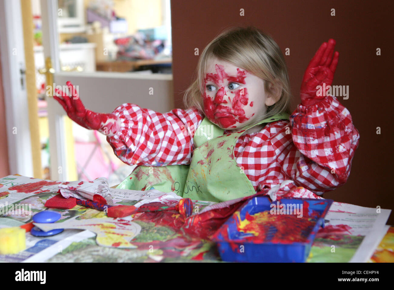 2 Year-Old girl enjoying making a mess with colourful paints at home. - Stock Image