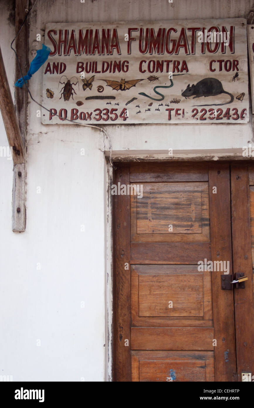Fumigation and Building contractor sign above doorway, Stone Town, Zanzibar - Stock Image