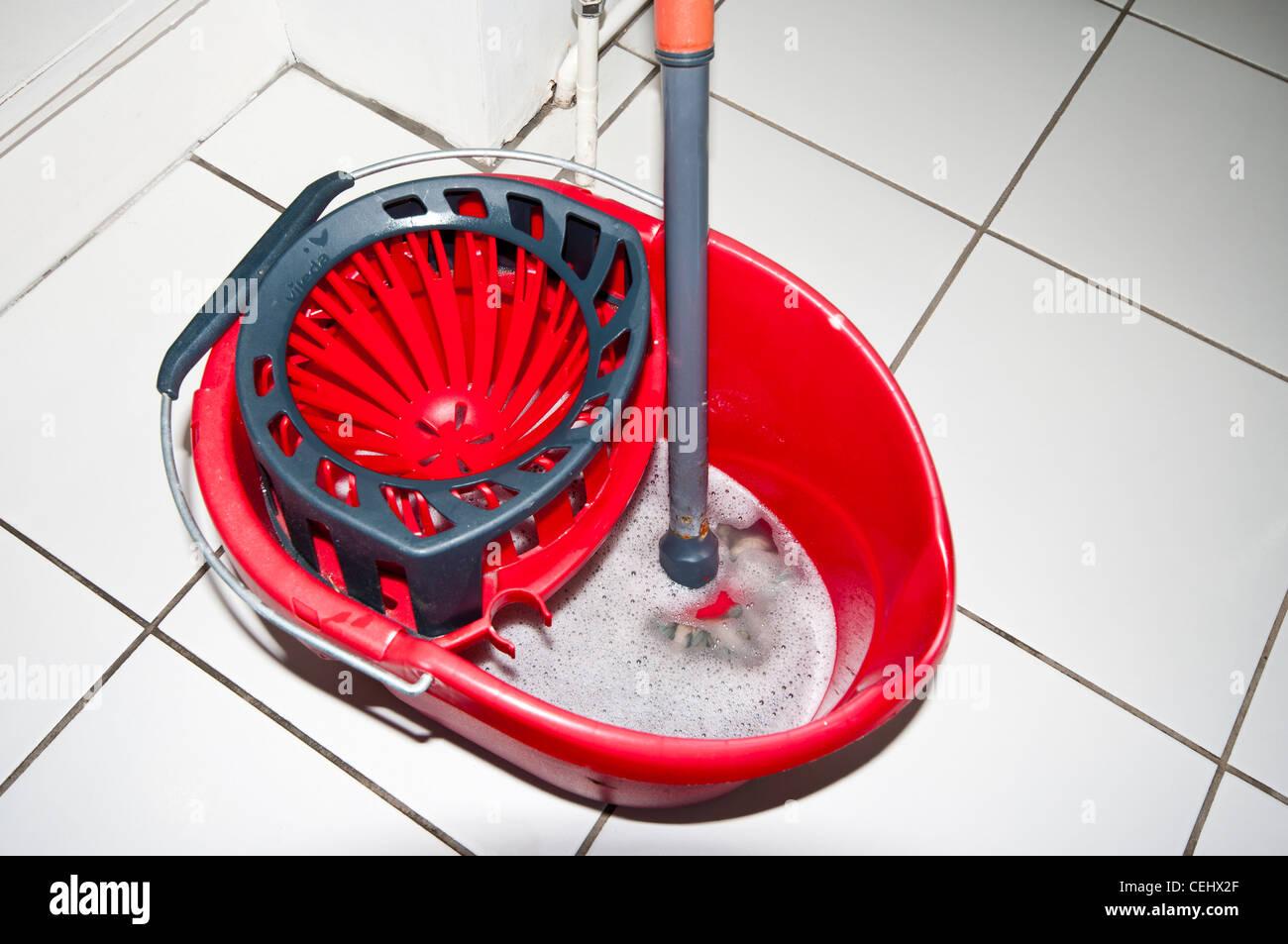 Red Plastic kitchen floor mop and bucket top view - Stock Image