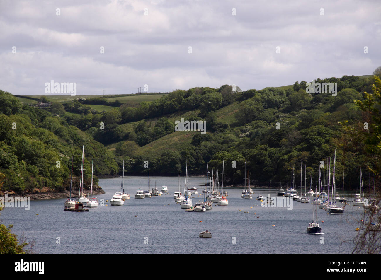 Fowey. View looking upstream of the River Fowey, with lots of boats anchored near Fowey and Polruan - Stock Image