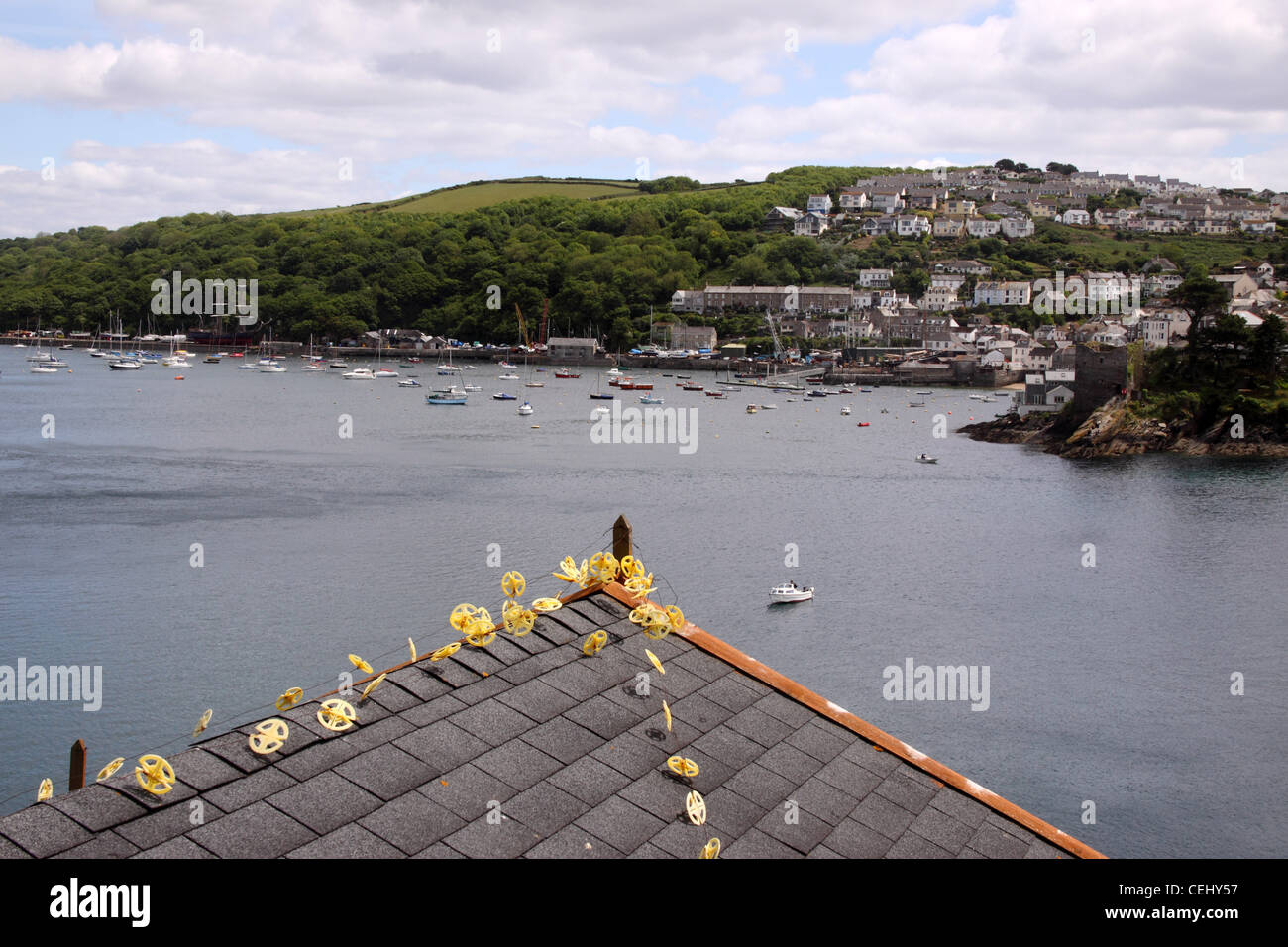 A seagull deterrent on a rooftop at Fowey, looking out over the river to Polruan, Cornwall. - Stock Image
