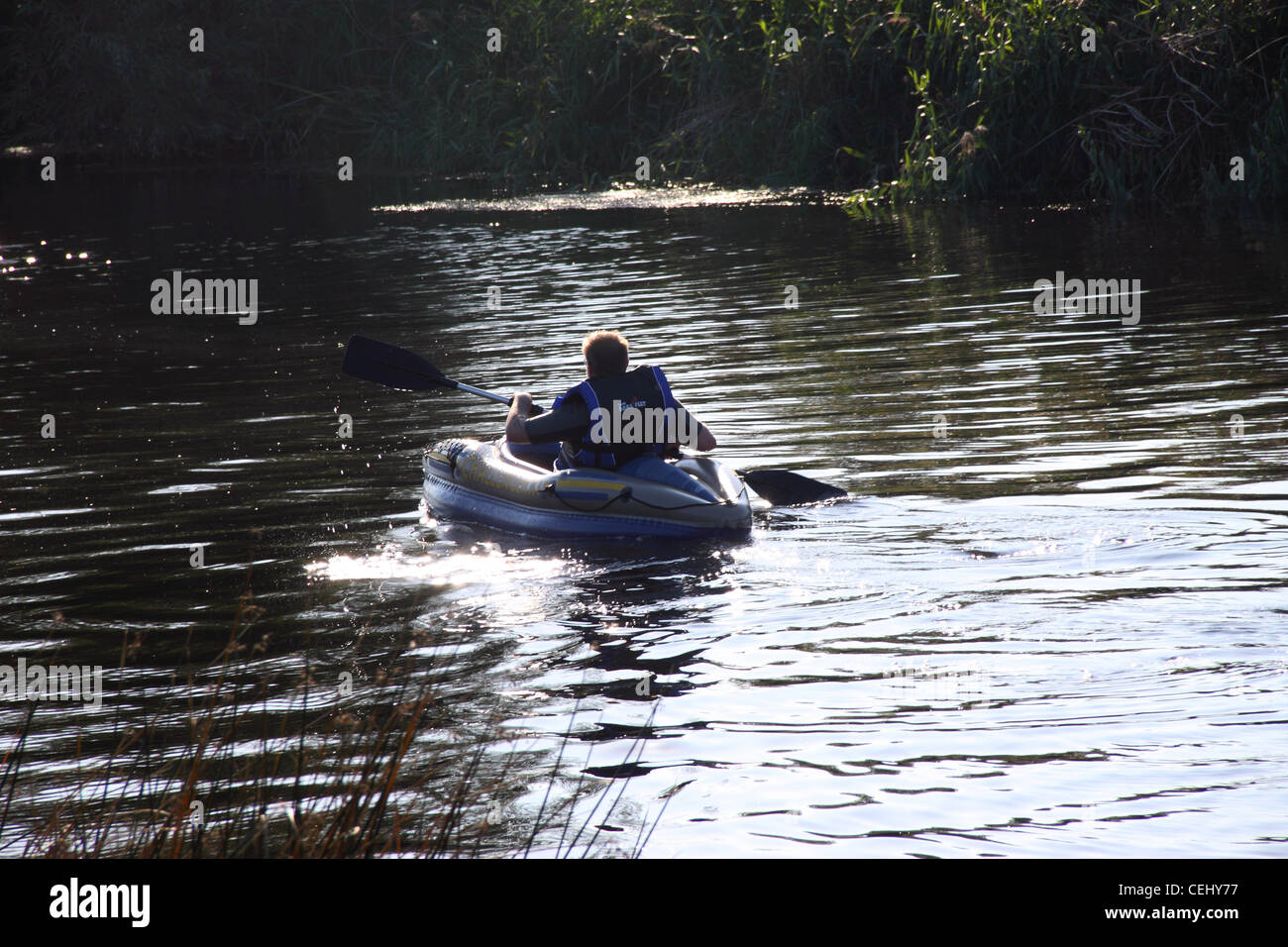 A man wearing a life jacket paddles a kayak away from camera, water splashing from the paddle, the river Avon, Bidford - Stock Image