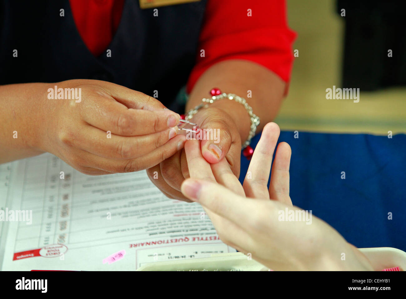Blood donor having finger pricked to test hemoglobin level in blood as you cannot donate blood if you are anaemic, - Stock Image