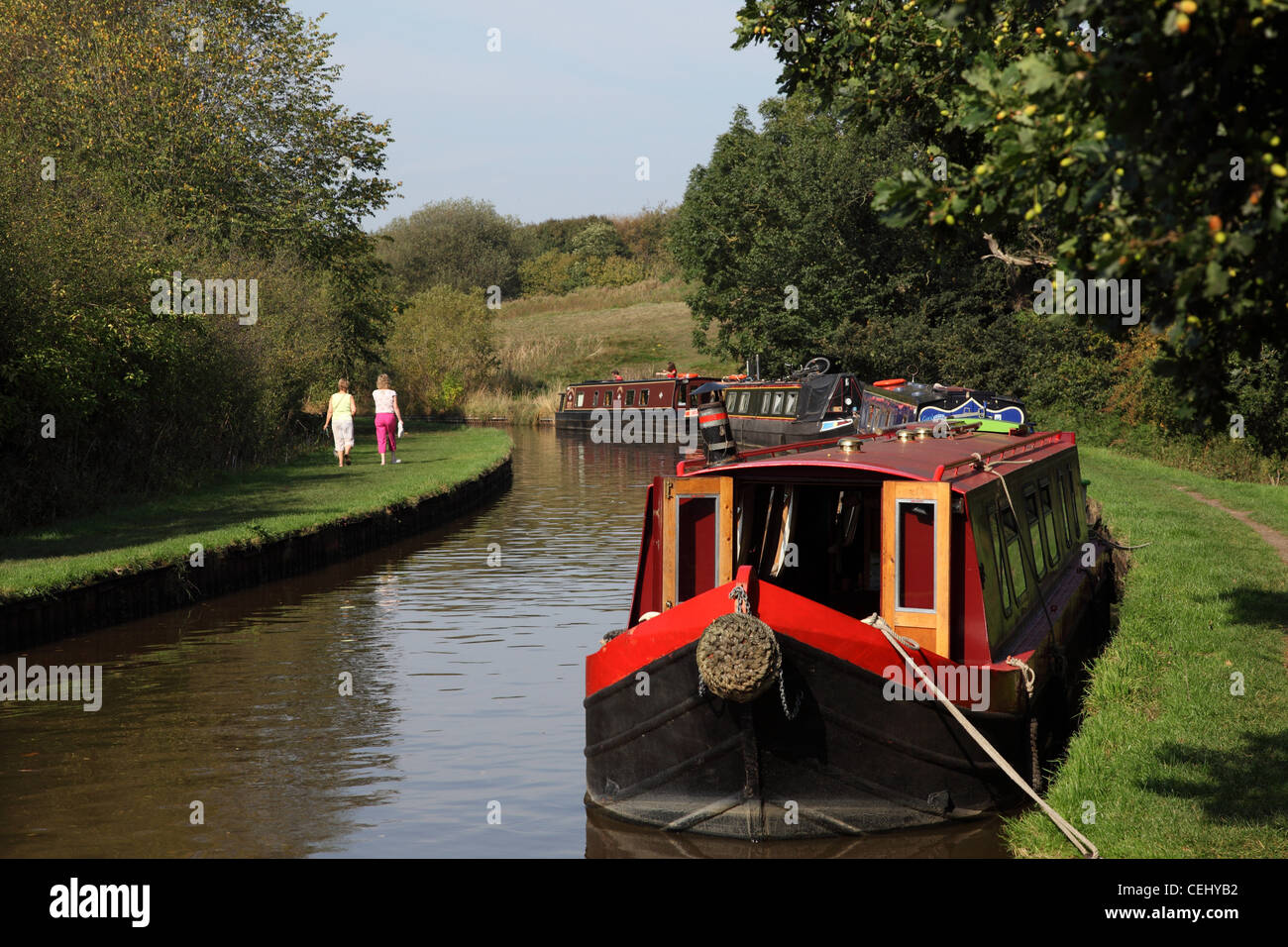 Canal boats on the Llangollen canal near Whitchurch, Shropshire UK, with people walking away from camera on the Stock Photo