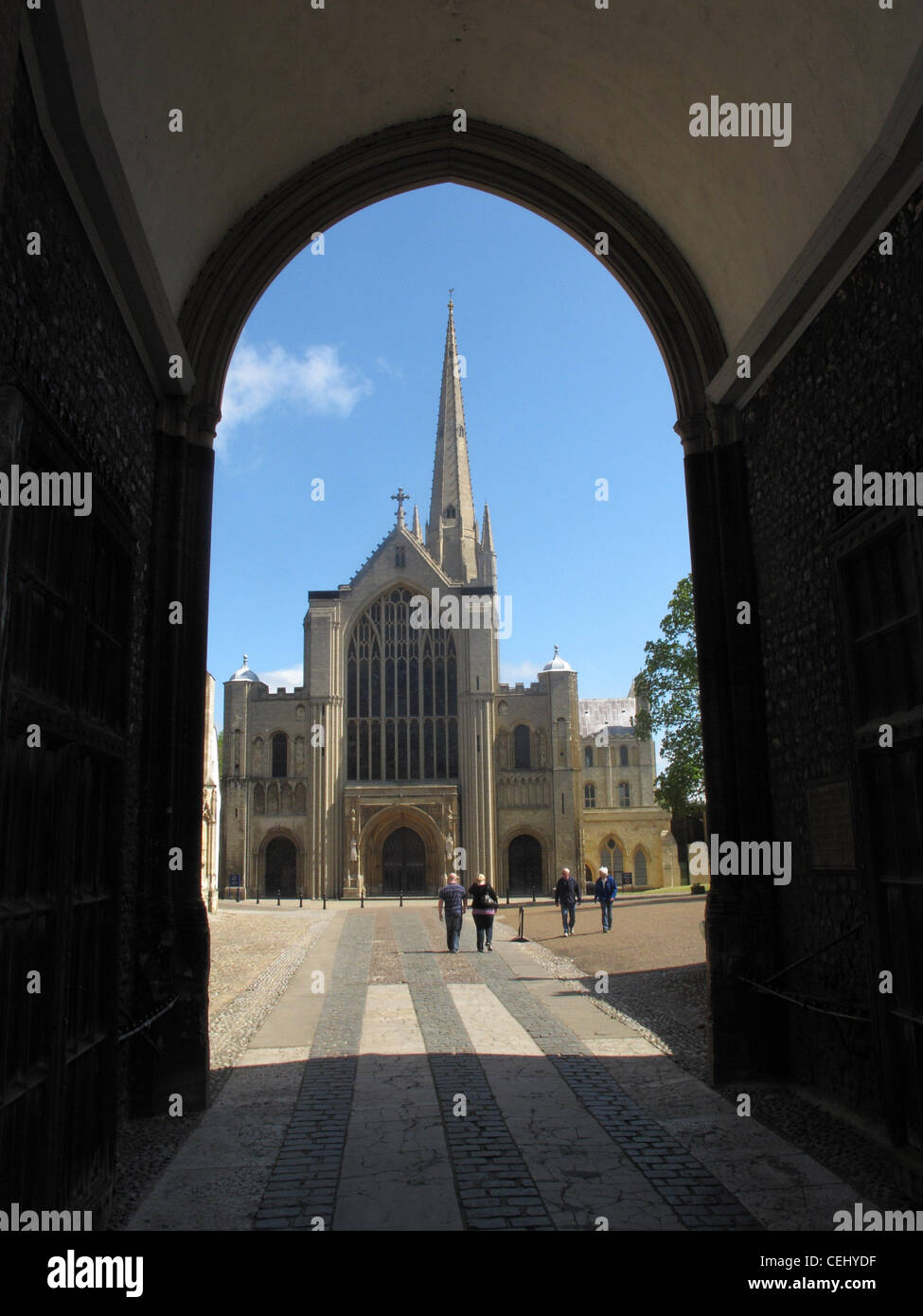 Norwich Cathedral, a 900 year old Benedictine inspired, Norman built centre of worship, viewed through an archway. - Stock Image