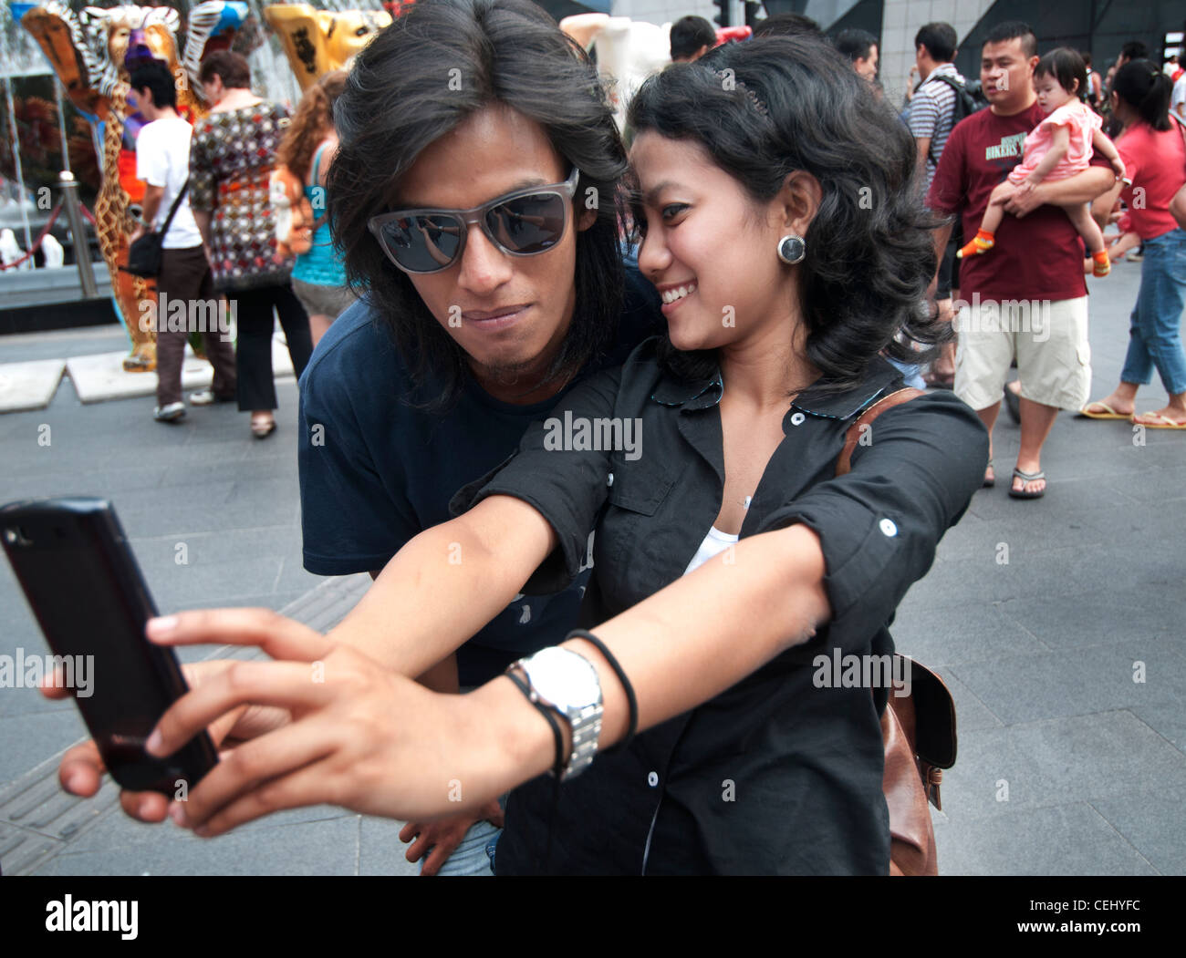 young couple watching their photograph at Bukit Bintang Kuala Lumpur - Stock Image