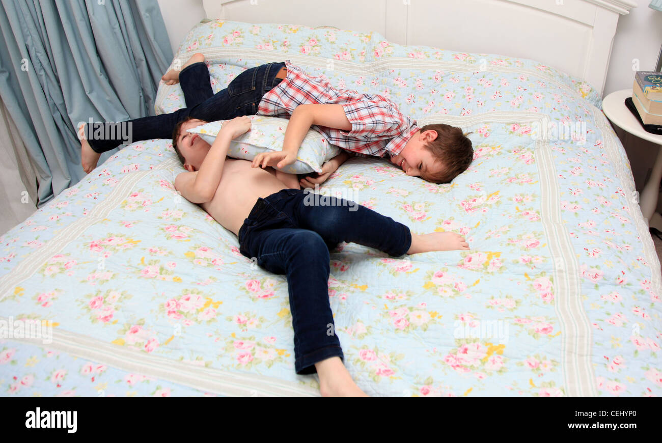 2 Boys Having A Pillow Fight On Bed