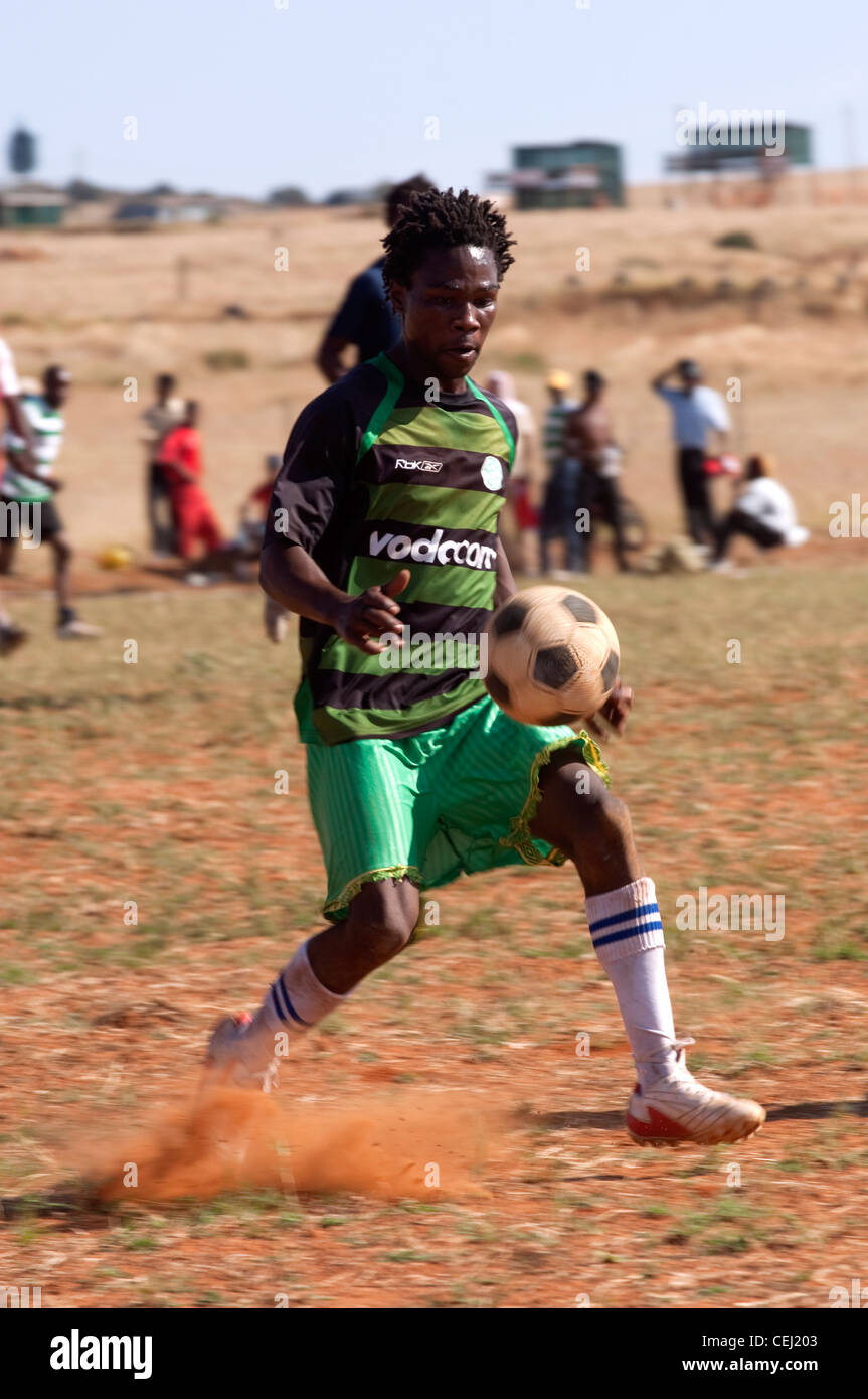 Soccer players on dusty rural field, outside Bloemfontein, Free State - Stock Image