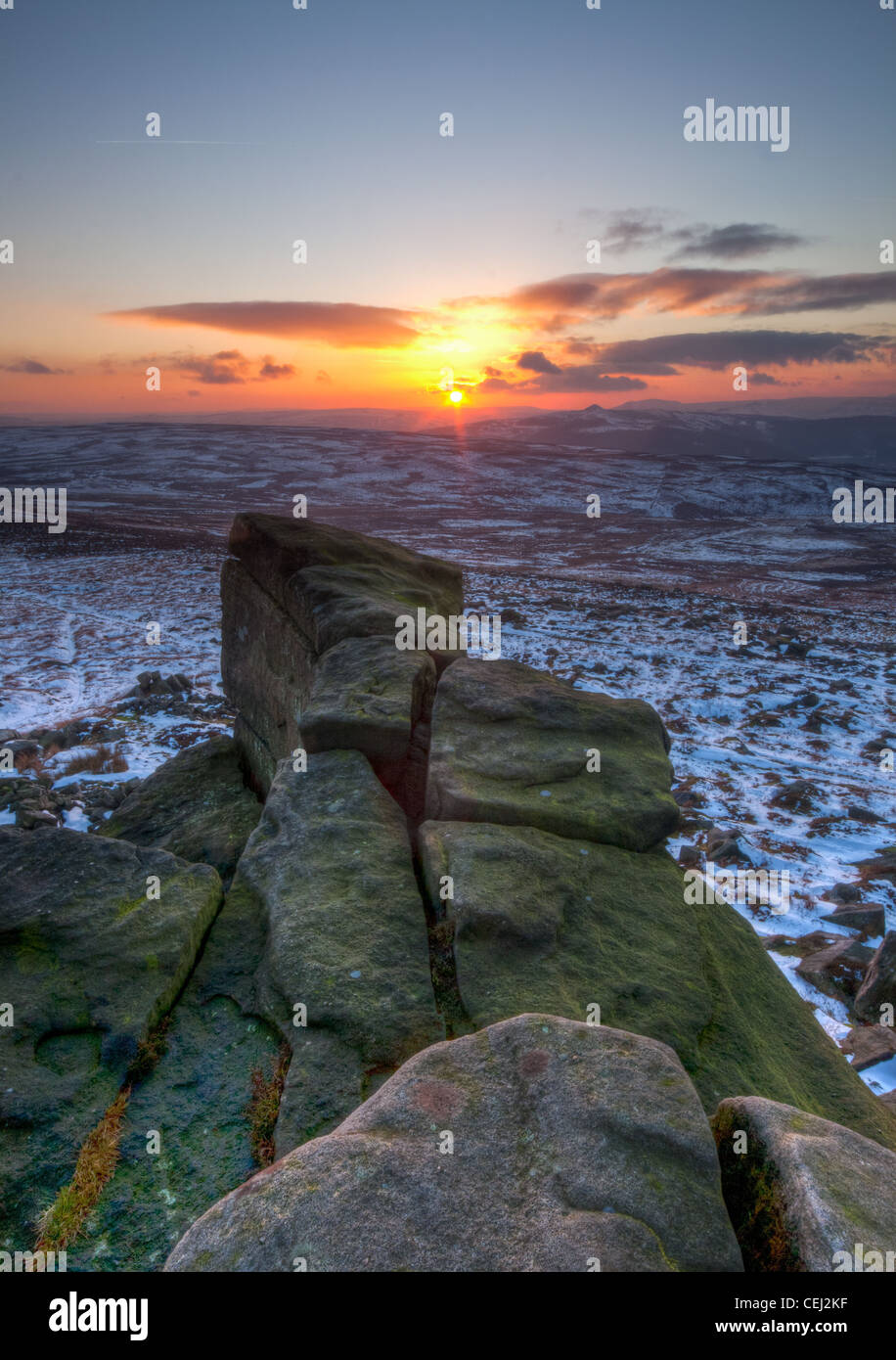 Sunset over a snowy landscape.  A rocky outcrop extends from the viewers feet to toward the sun setting just above - Stock Image