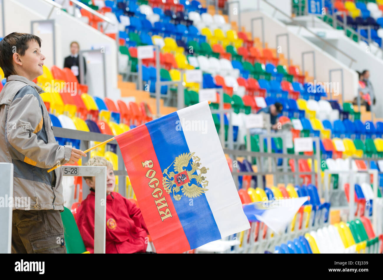 Young ice-hockey fans with flag of Russia inside arena - Stock Image