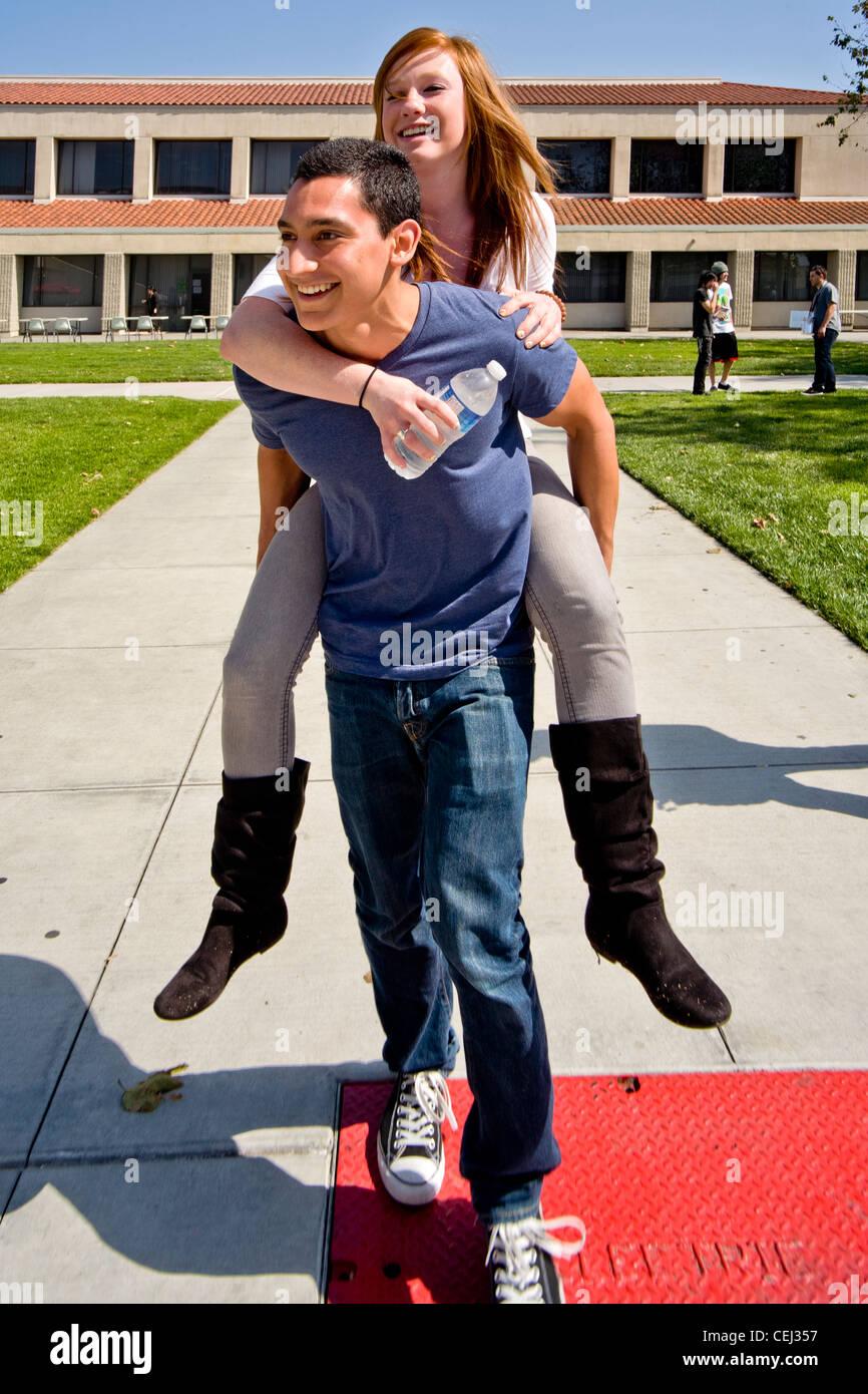 a hispanic student carries his caucasian girlfriend piggyback across