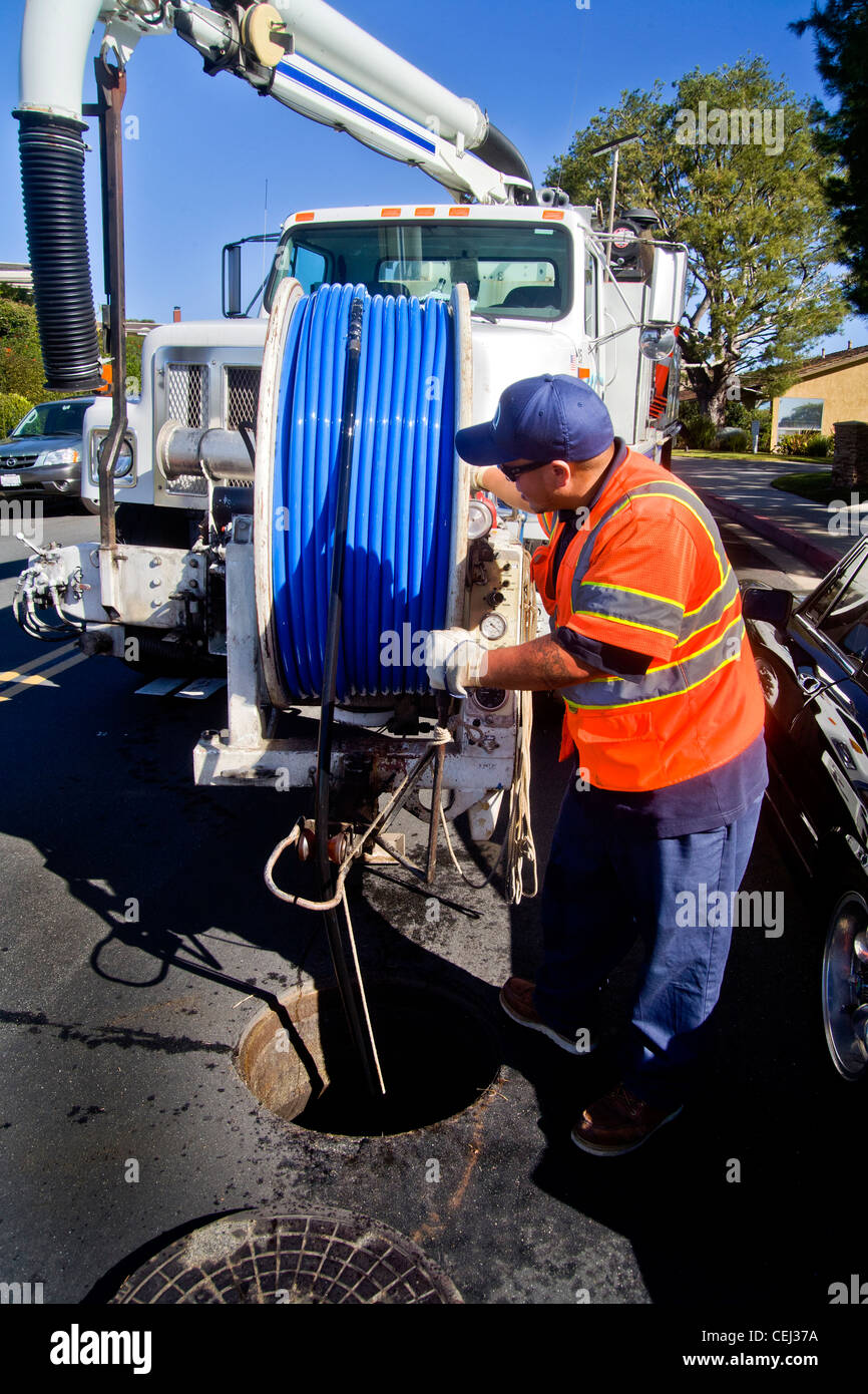 Using a truck mounted suction system, a technician cleans a clogged sewer in Laguna Niguel, CA - Stock Image