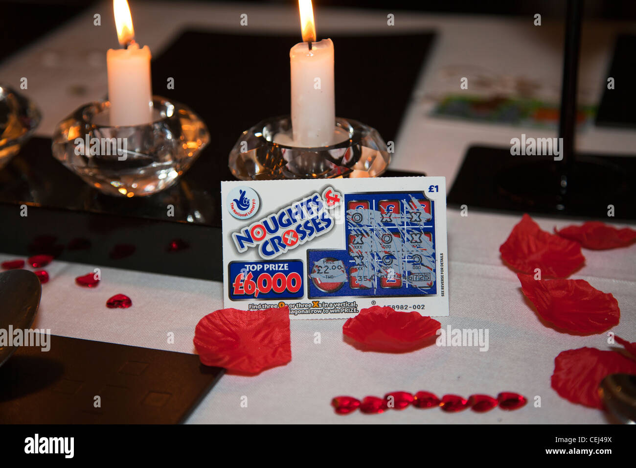 Winning scratch card £2 win leant up against candles on table - Stock Image