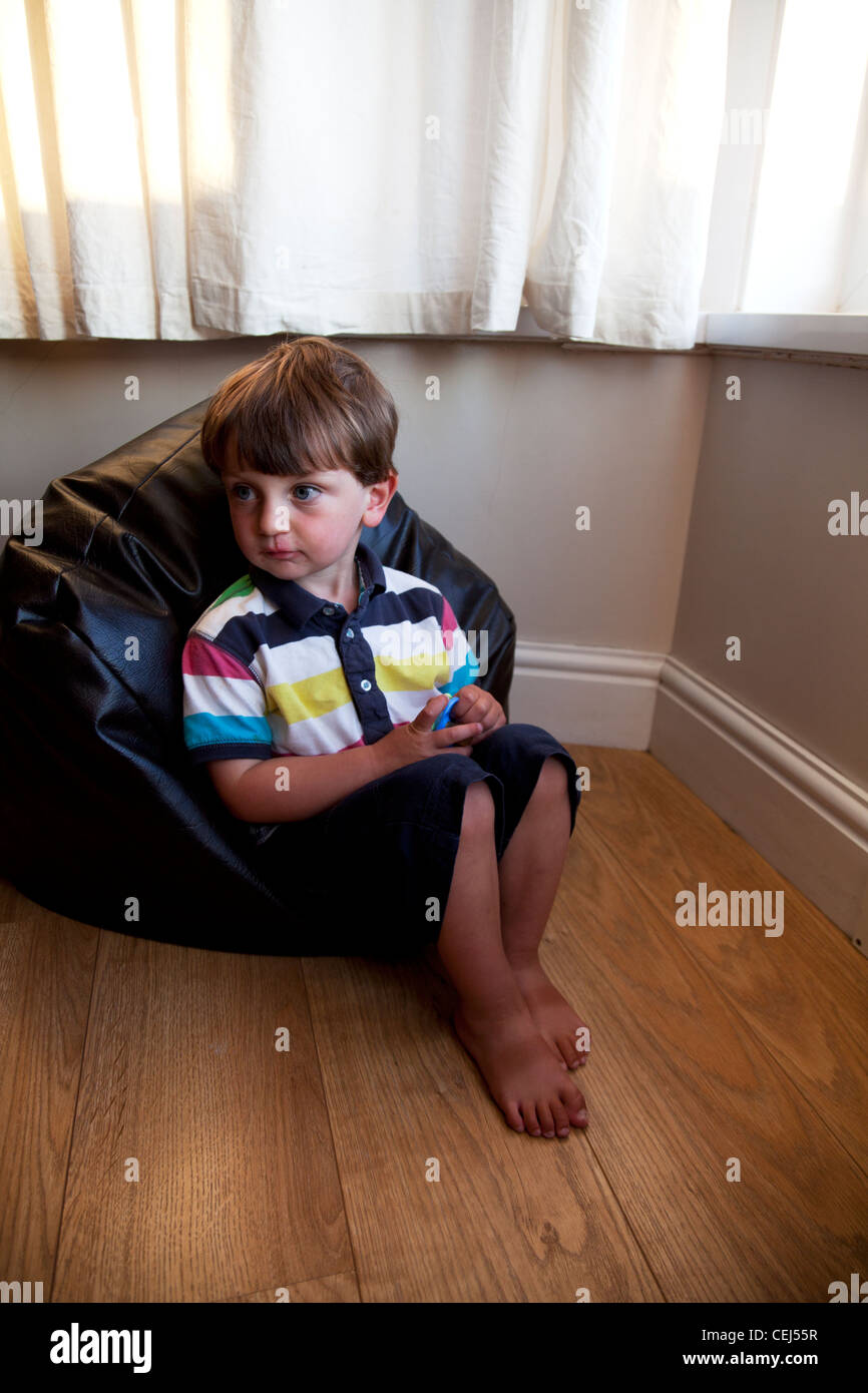 Young boy looking to one side sat on bean bag huge eyes cute kid Stock Photo