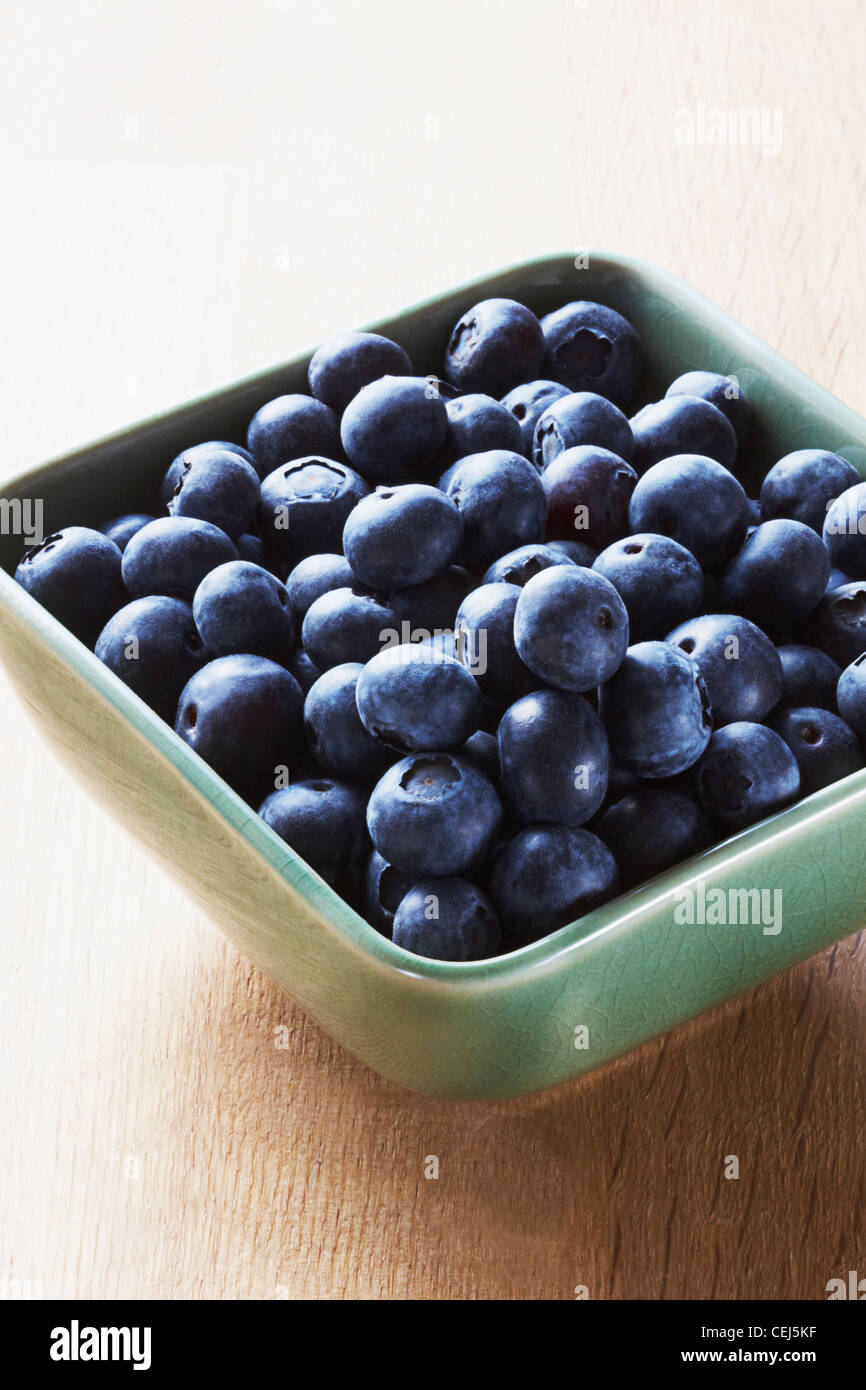 Blueberries in a green bowl on a wooden background - Stock Image