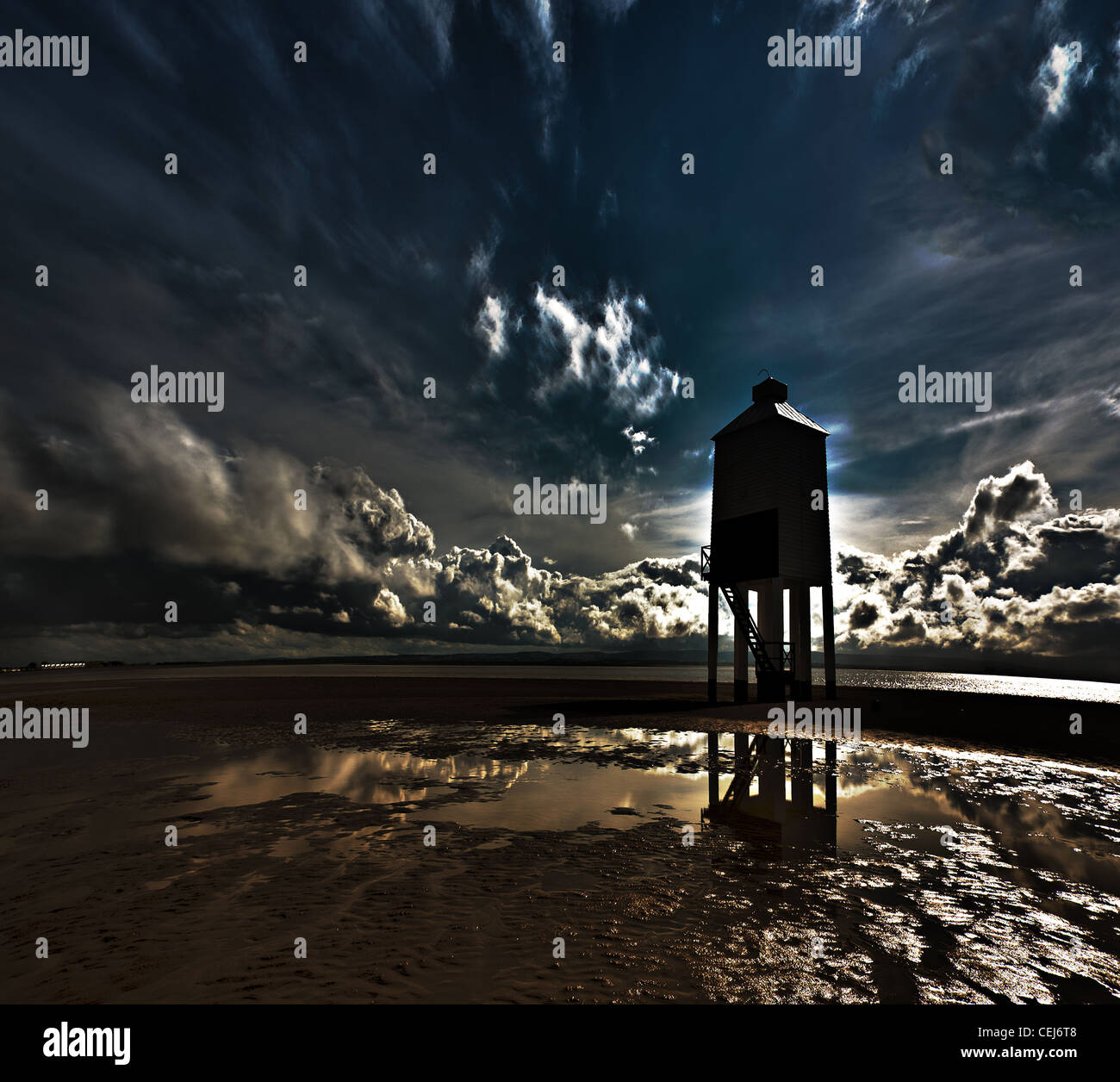 A black and white and colour photograph of a wooden lighthouse at dawn and low tide, shot in Somerset, UK Stock Photo