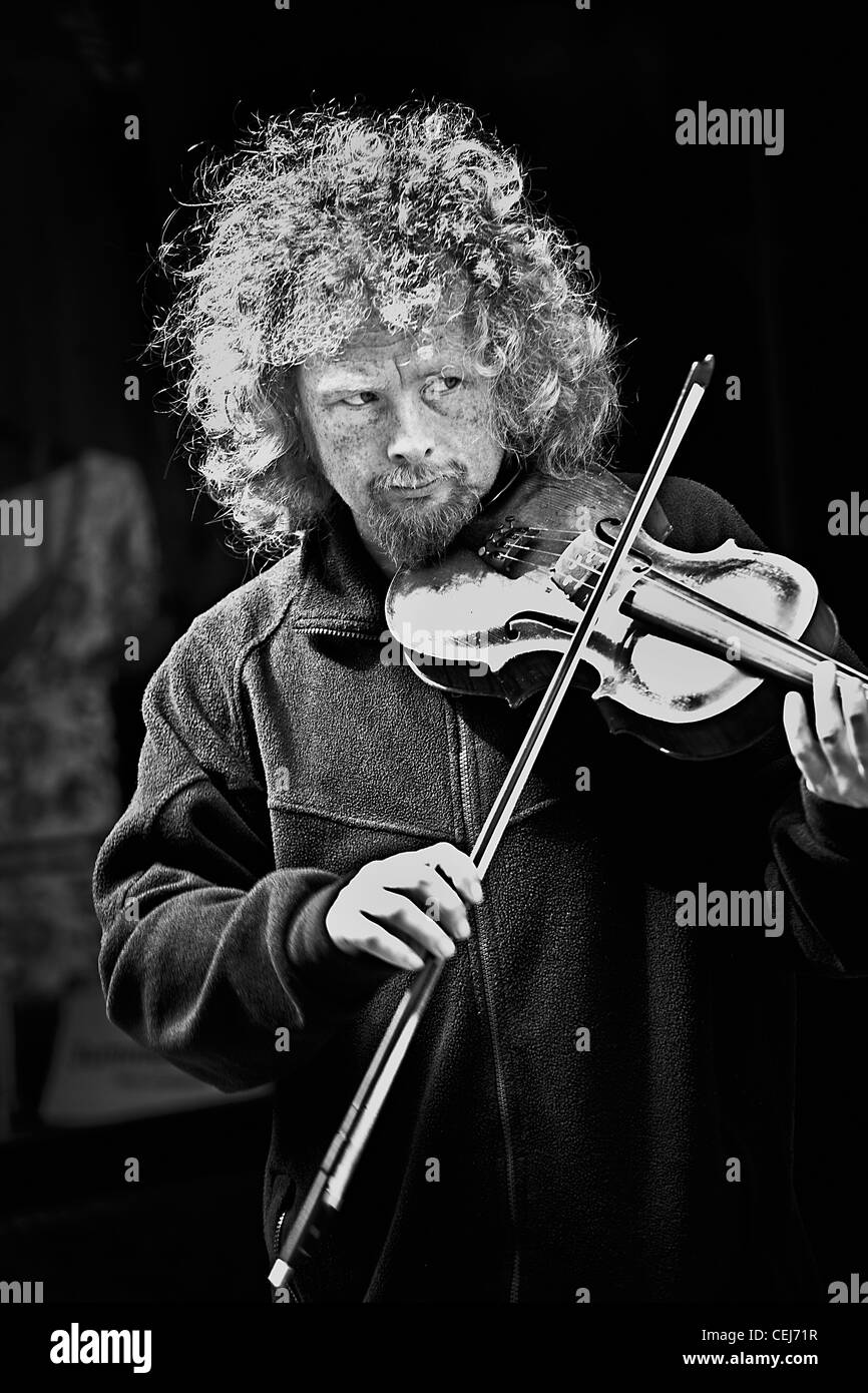 A black and white portrait of a white man age 30-35 busking,playing a violin on the streets of London. - Stock Image