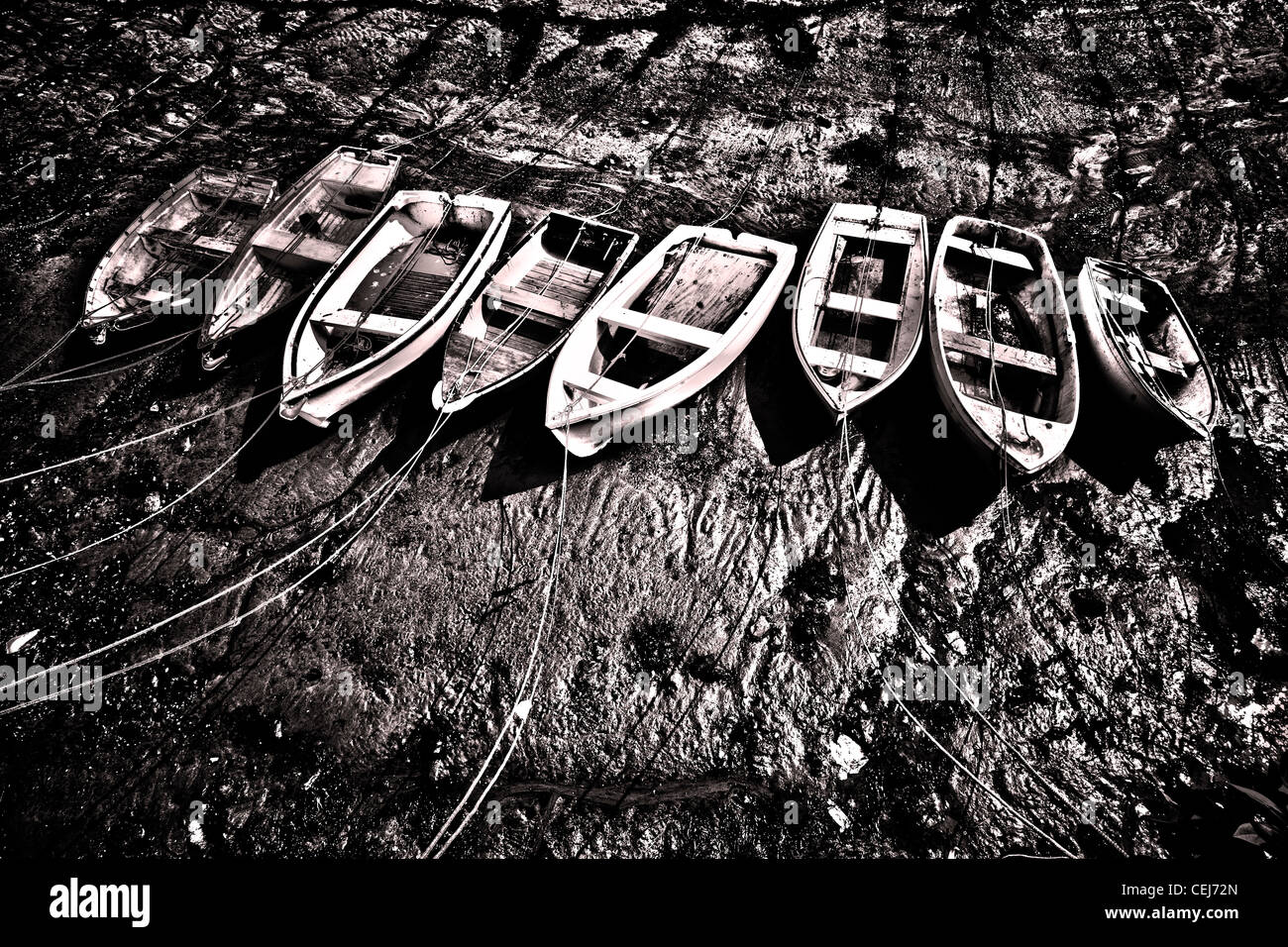 A colour and black and white image of rowing boats tied up at low tide. - Stock Image