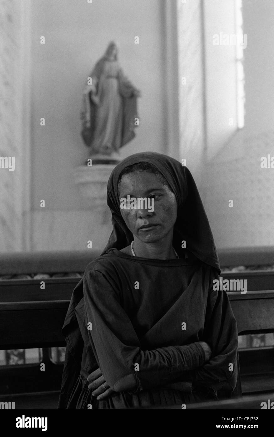 Woman in church, Catholicism. Pilgrimage to Juazeiro do Norte city in Ceara State, Northeastern Brazil - Stock Image