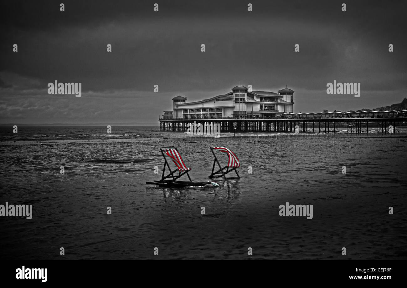 Red and white striped deck chairs on Weston Super Mare Beach.   Weston Super Mare Pier.  British Seaside. - Stock Image