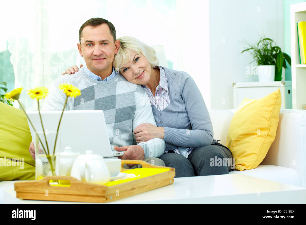 Portrait of affectionate senior couple looking at camera and smiling - Stock Image