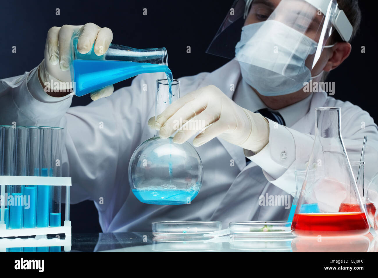 Scientist pouring fluid substances from one beaker into another - Stock Image