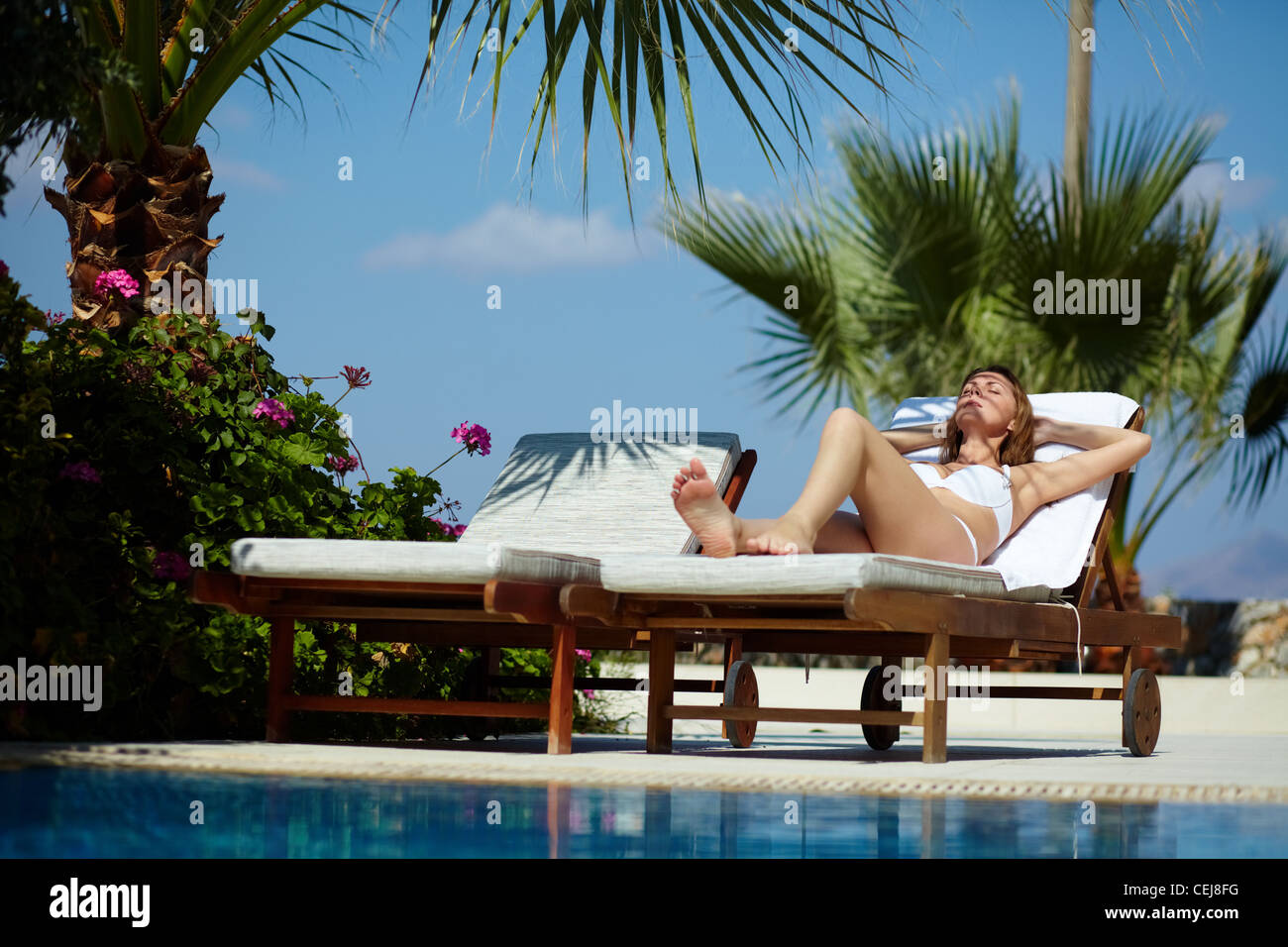 Young woman sunbathing by the pool - Stock Image