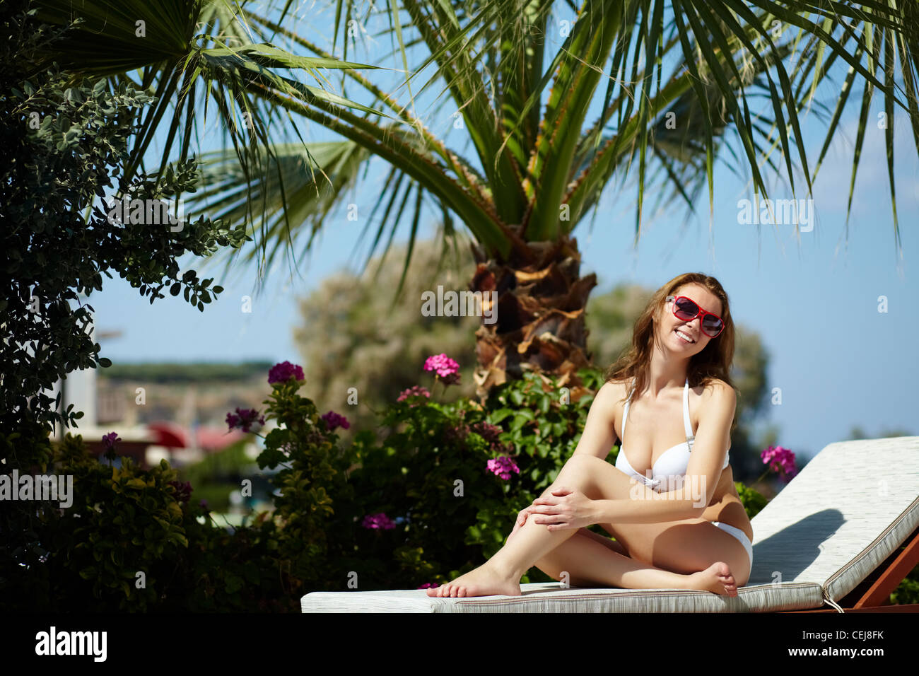 Attractive woman sitting on chaise lounge and smiling at camera - Stock Image