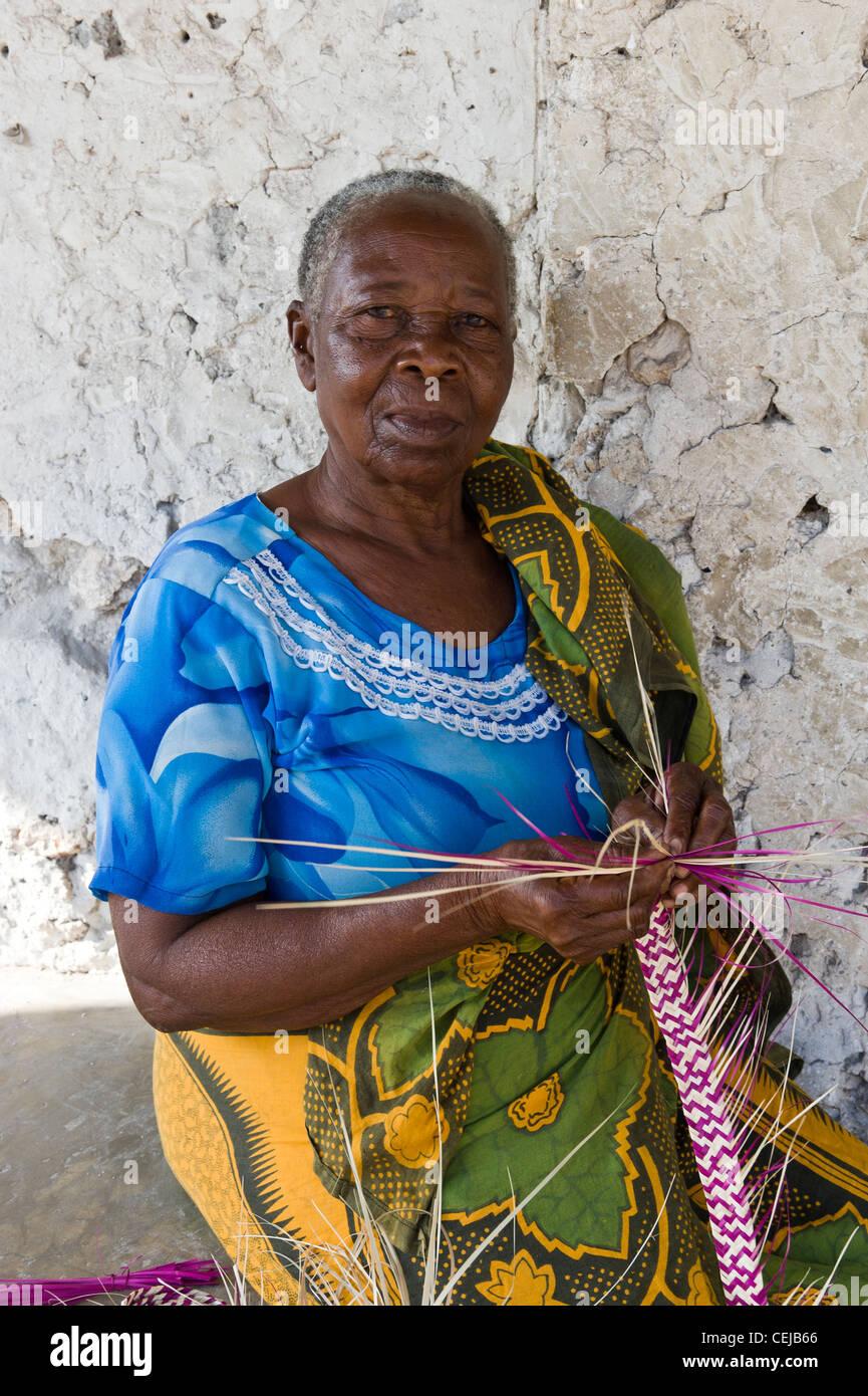 Woman weaving stripes using palm fronds in Bwejuu village east coast of Zanzibar Tanzania - Stock Image