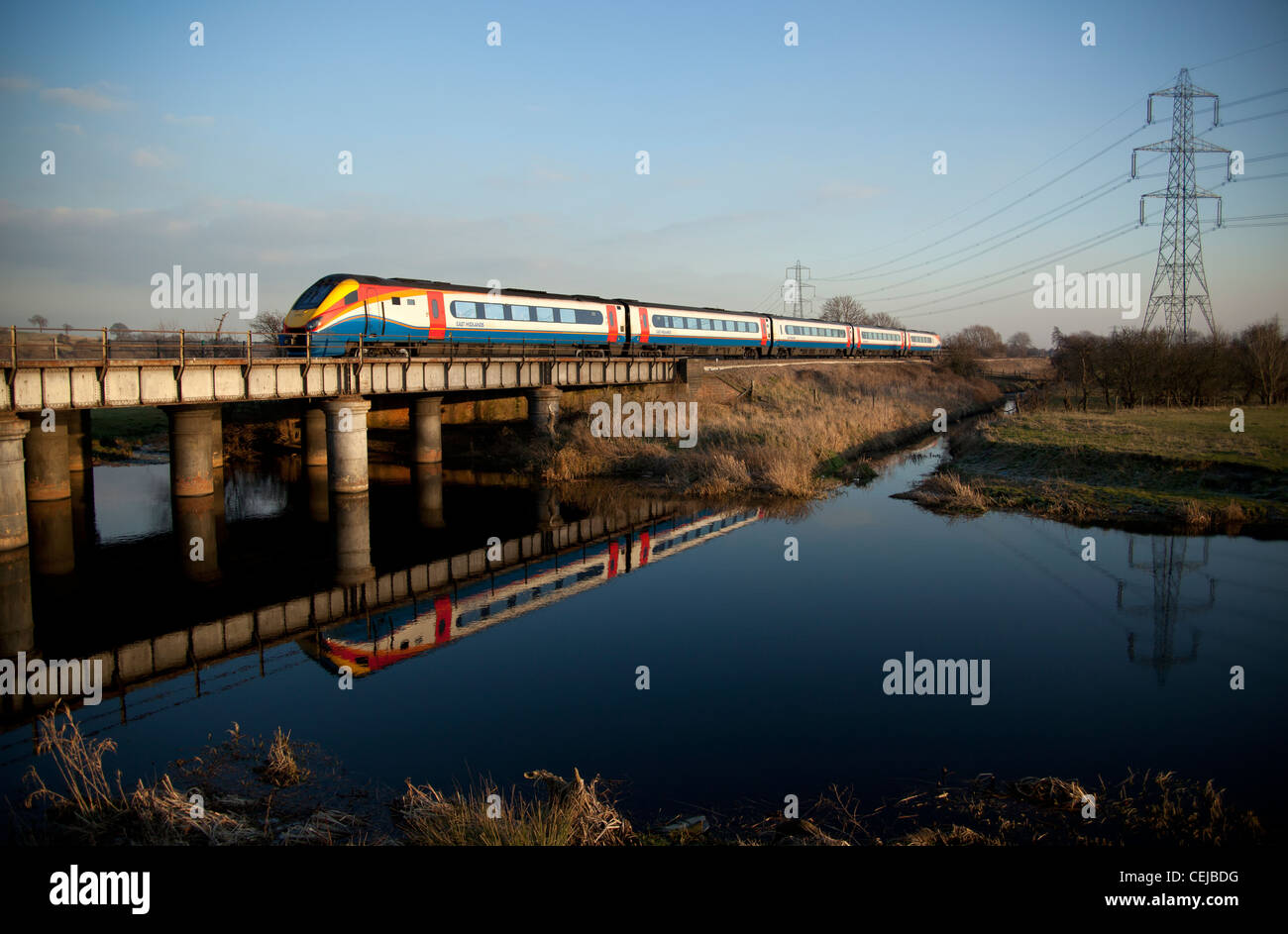 East Midlands Trains class 222 Meridian DMU passenger train reflecting in the River Soar Normanton on Soar, Loughborough,England - Stock Image