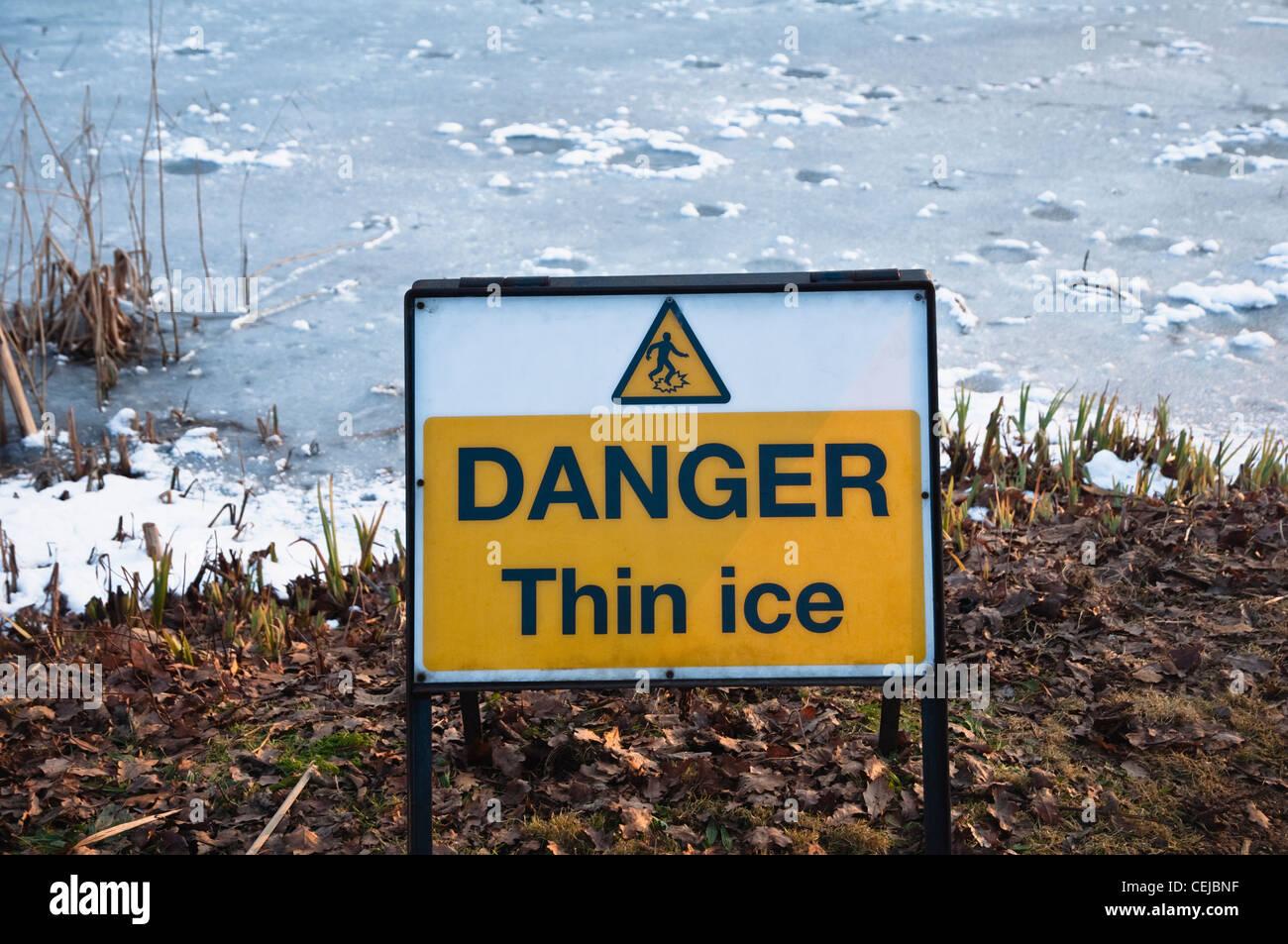 'Danger Thin Ice' sign beside frozen water. - Stock Image