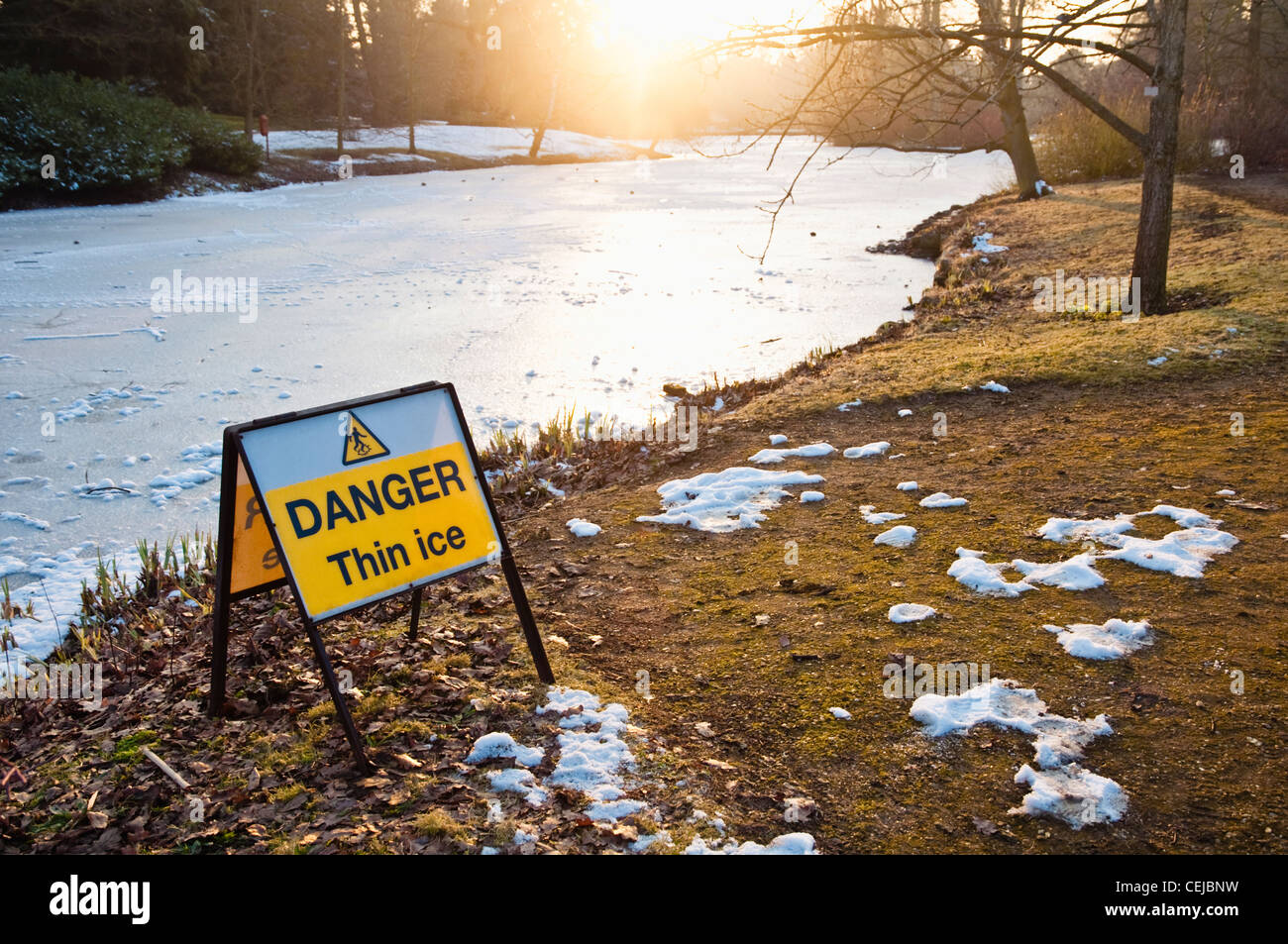 'Danger Thin Ice' sign beside a frozen lake lit up with winter sunshine. UK - Stock Image
