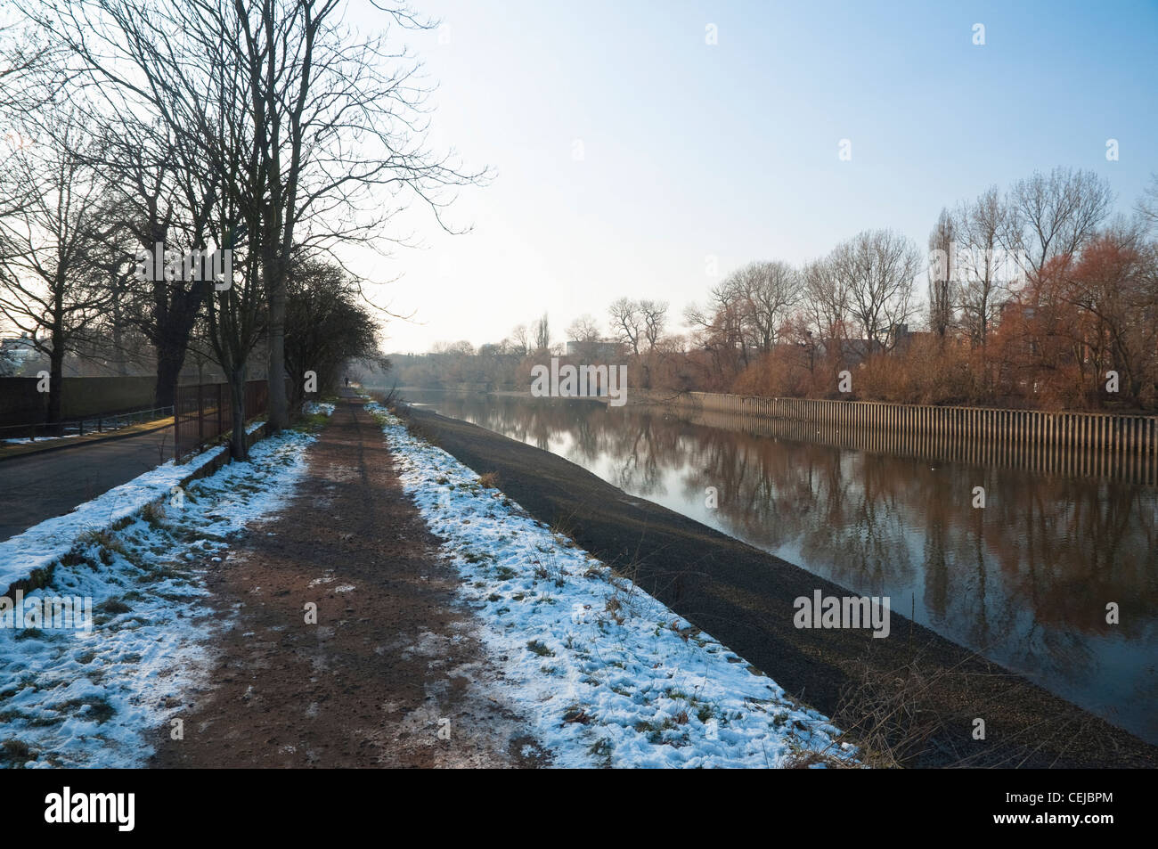 Winter view of the towpath along the River Thames. Viewed from the Kew Bridge bank looking across the river to Brentford. Stock Photo