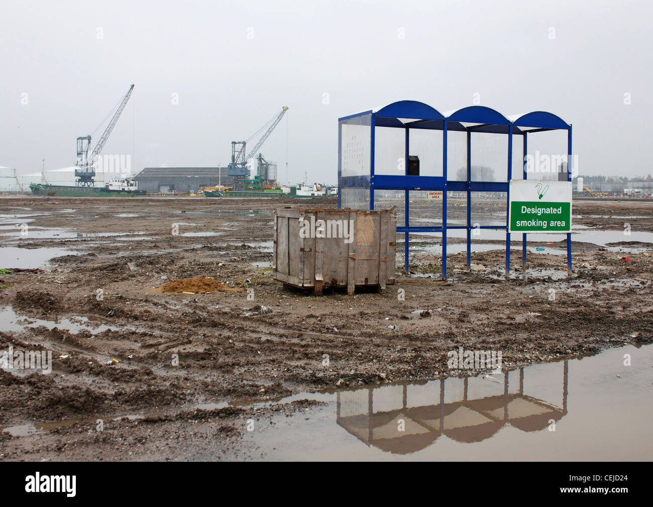 Smokers' shelter standing alone in a wasteland of mud and pools of water, Trafford Park, Manchester, England - Stock Image