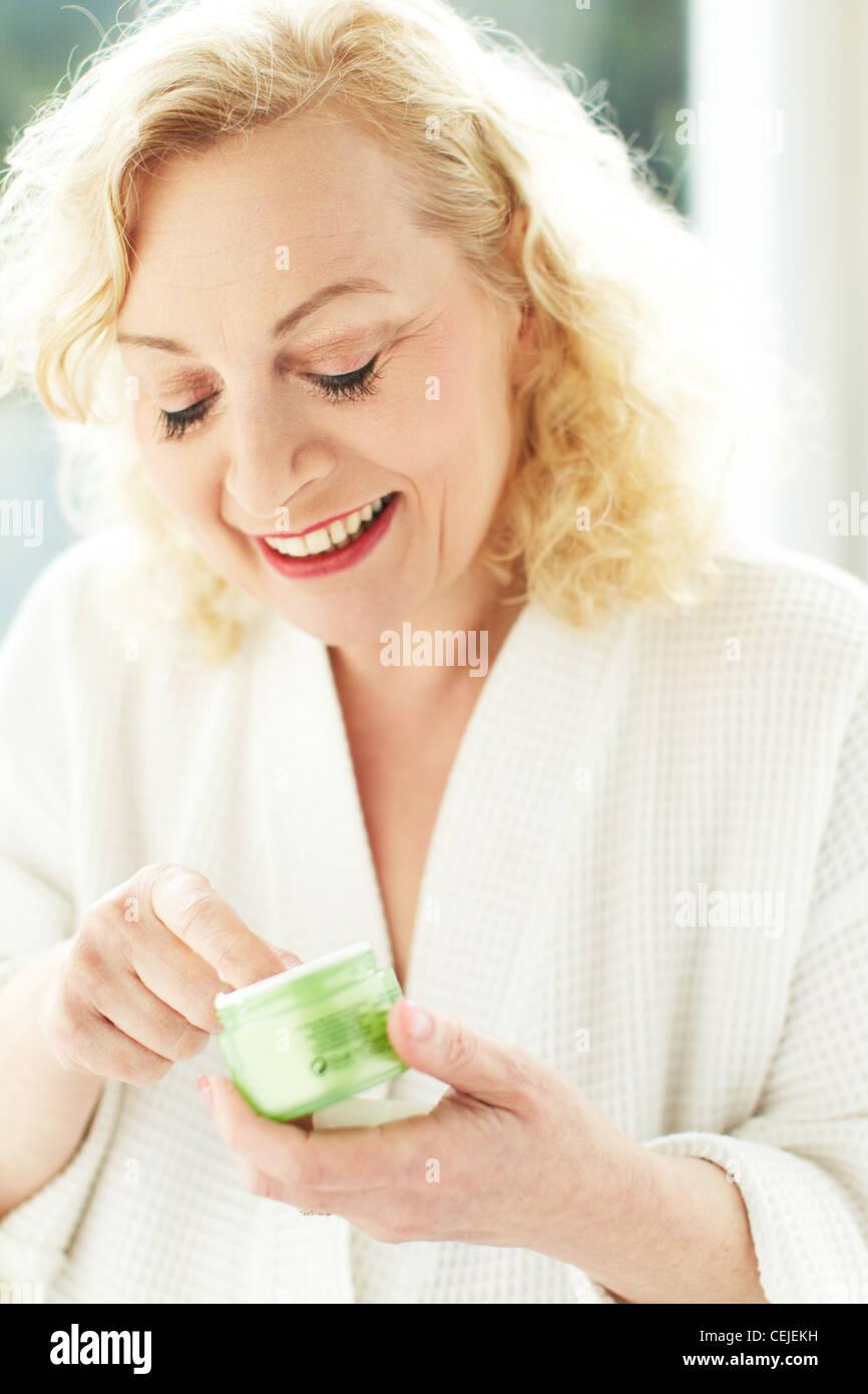 Woman applying face cream - Stock Image
