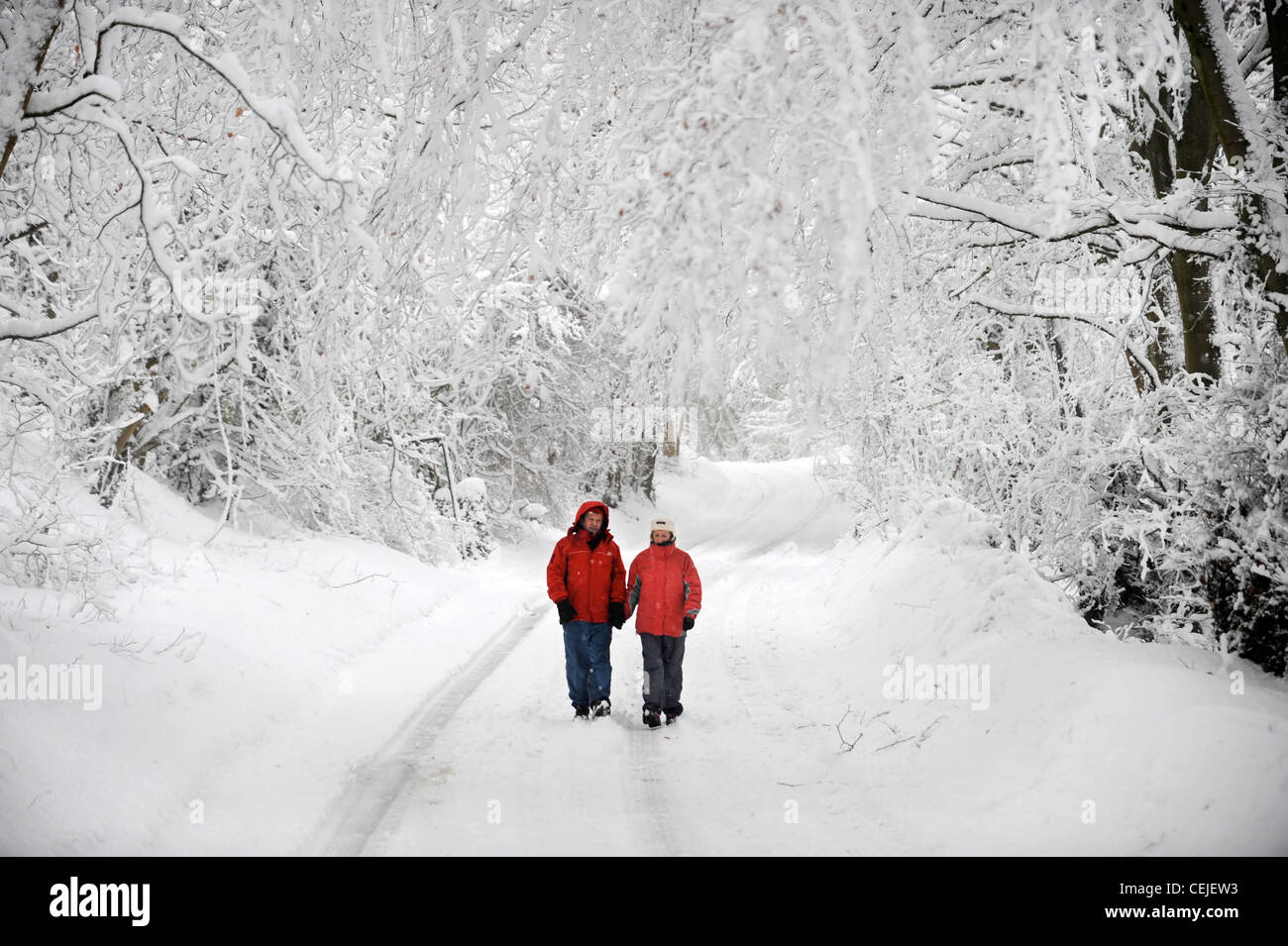 A couple in matching red winter coats walking in a Cotswold lane in snowy conditions UK - Stock Image