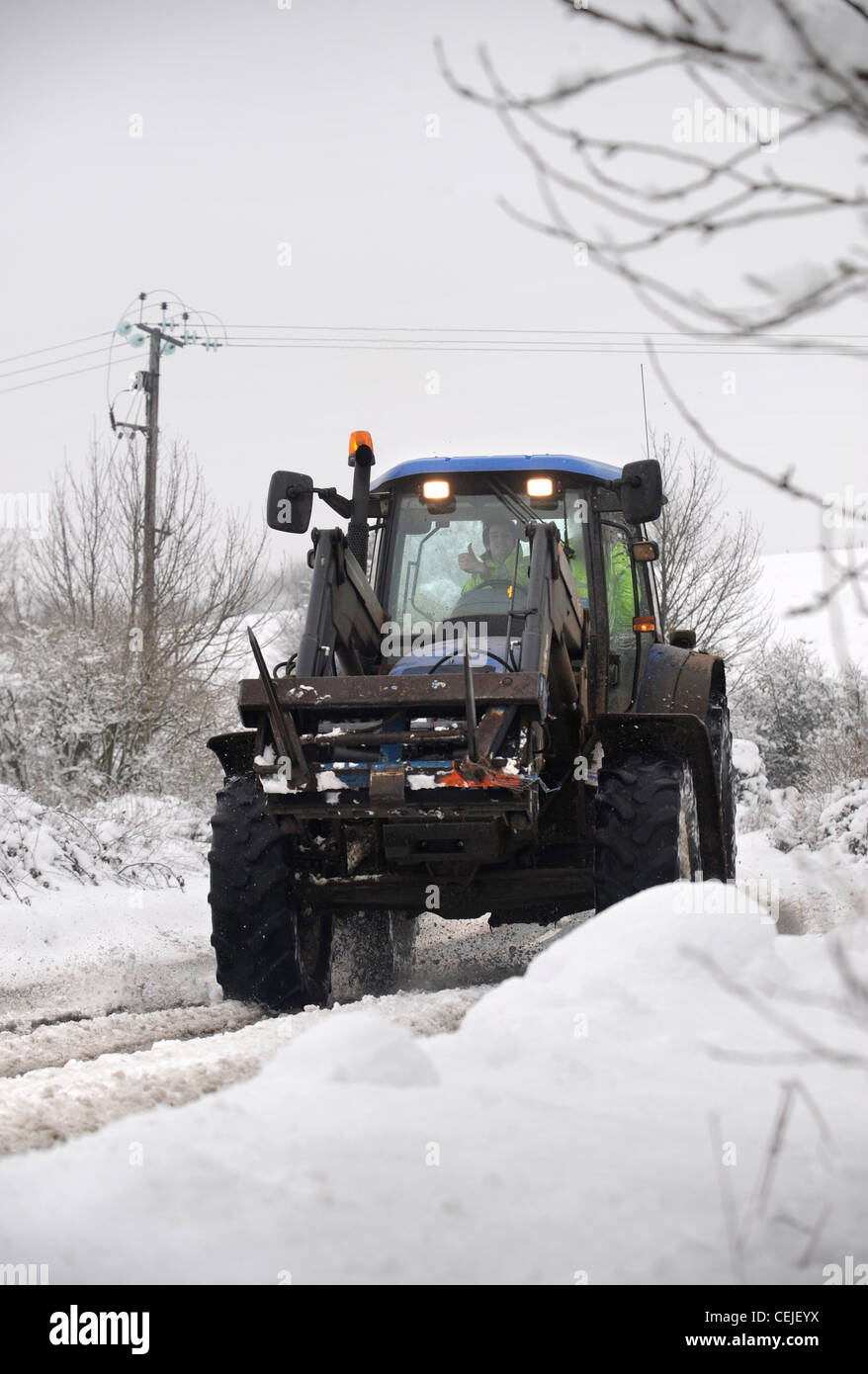 A farmers tractor in snow Gloucestershire UK - Stock Image
