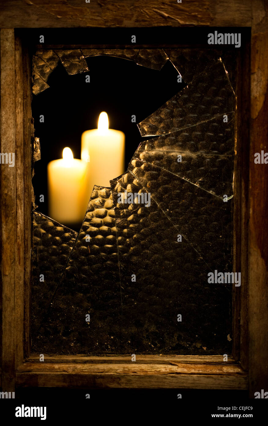A broken glass window pane with lit candles - Stock Image