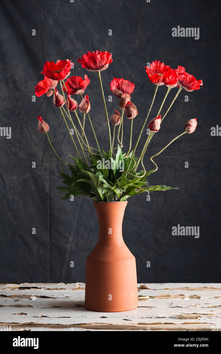 A pottery vase of artificial red poppies - Stock Image