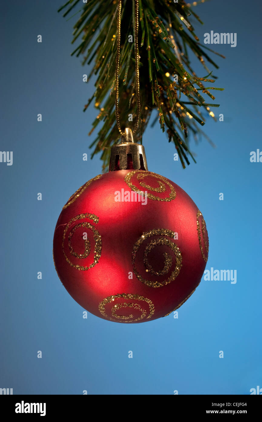 A red Christmas ball decoration against a blue background - Stock Image